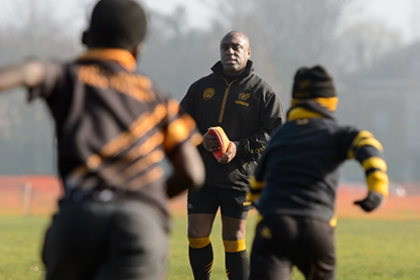 A junior rugby coach watches on as two players run towards him