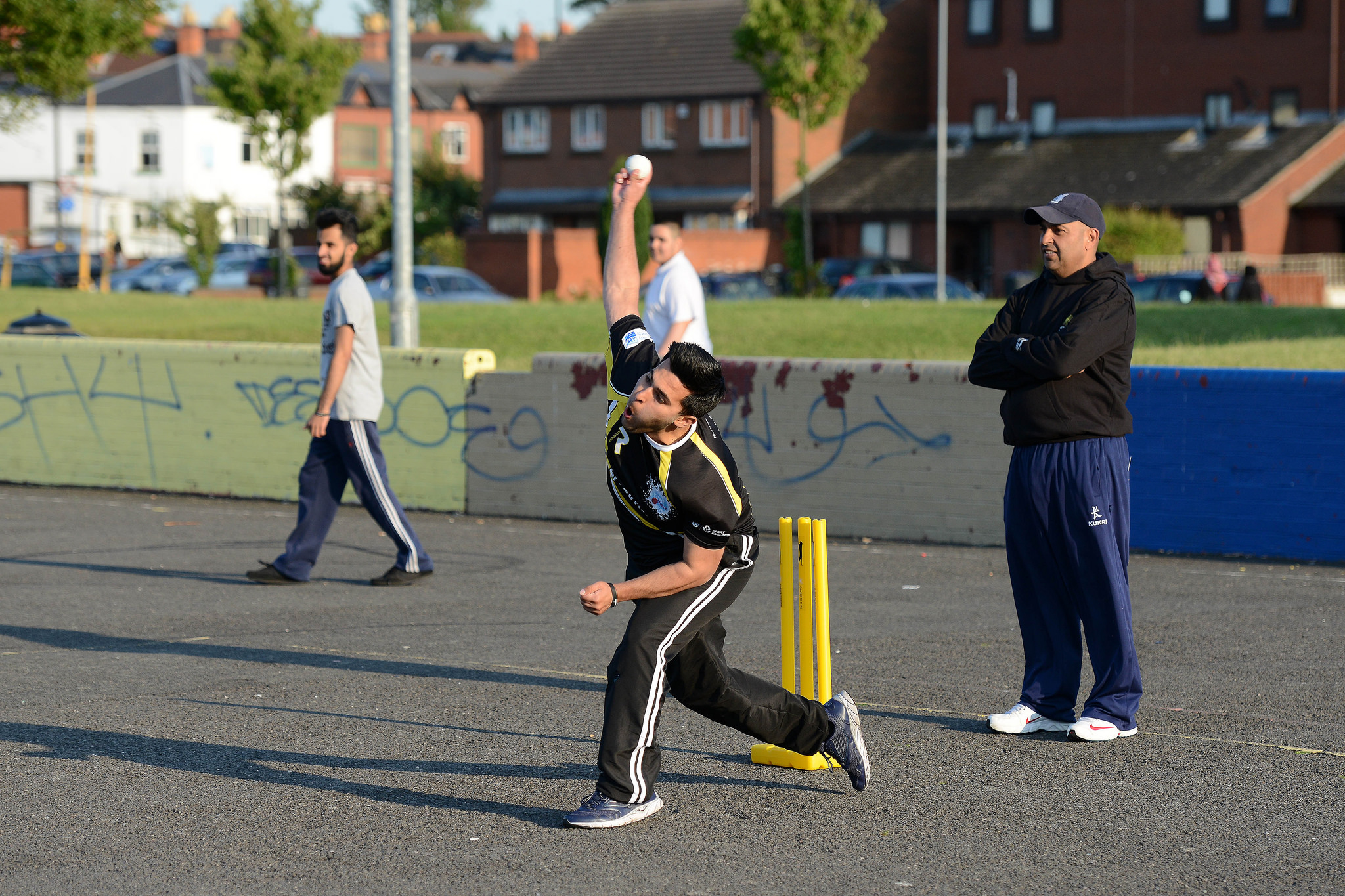 A teenage boy bowls a cricket ball as his coach watches on