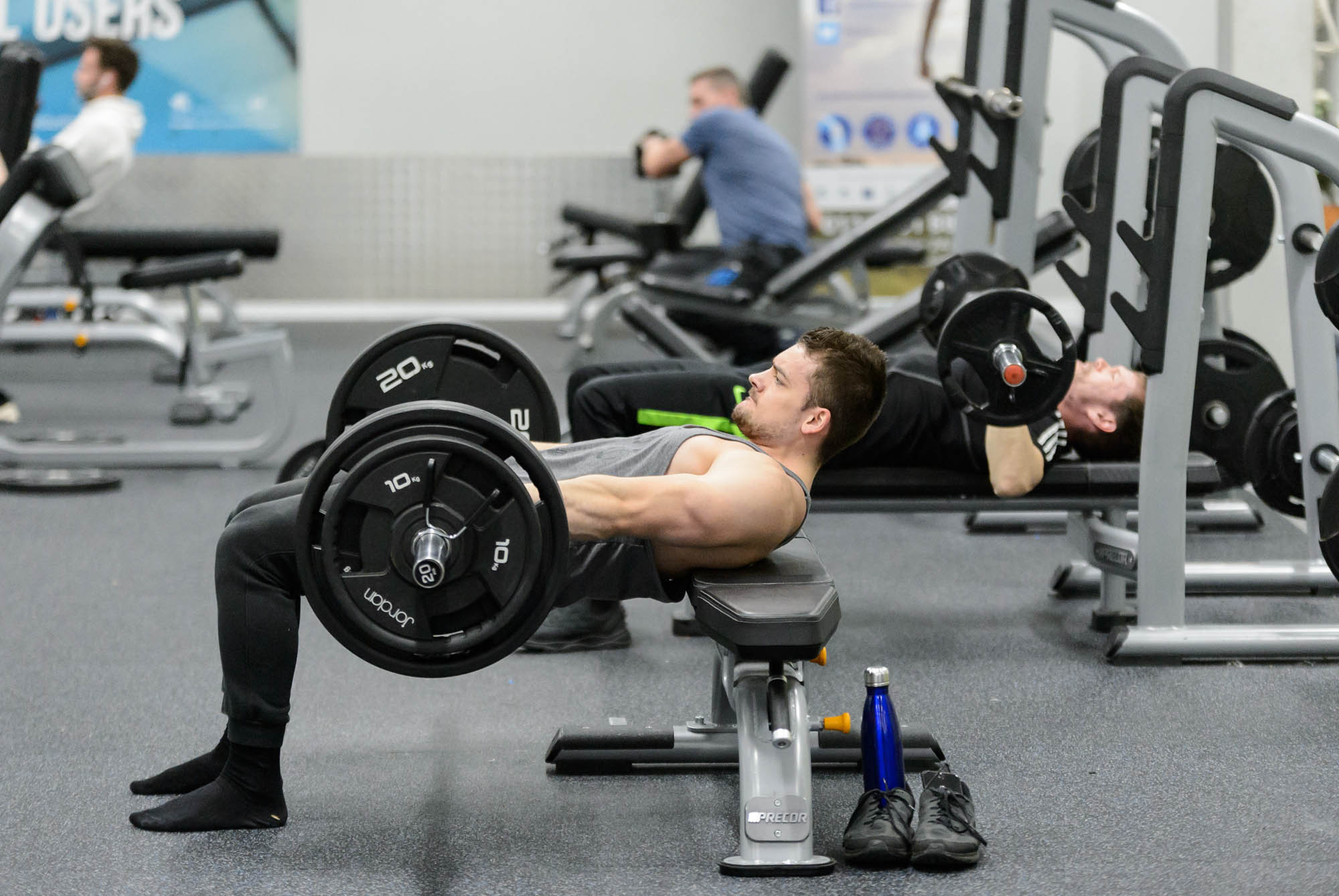 A man does some heavy free weights in a gym