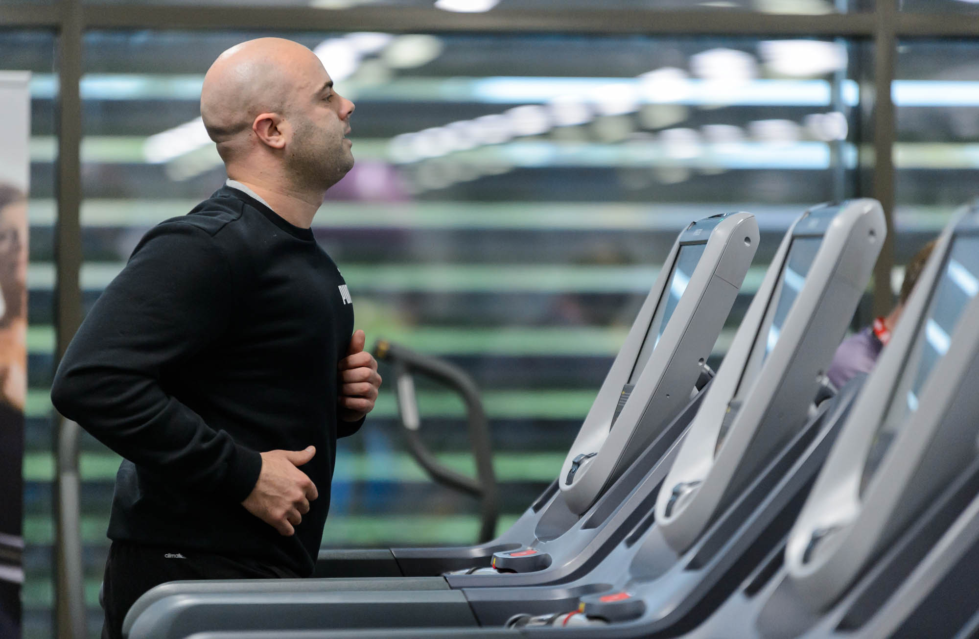 A man runs on a treadmill in a gym