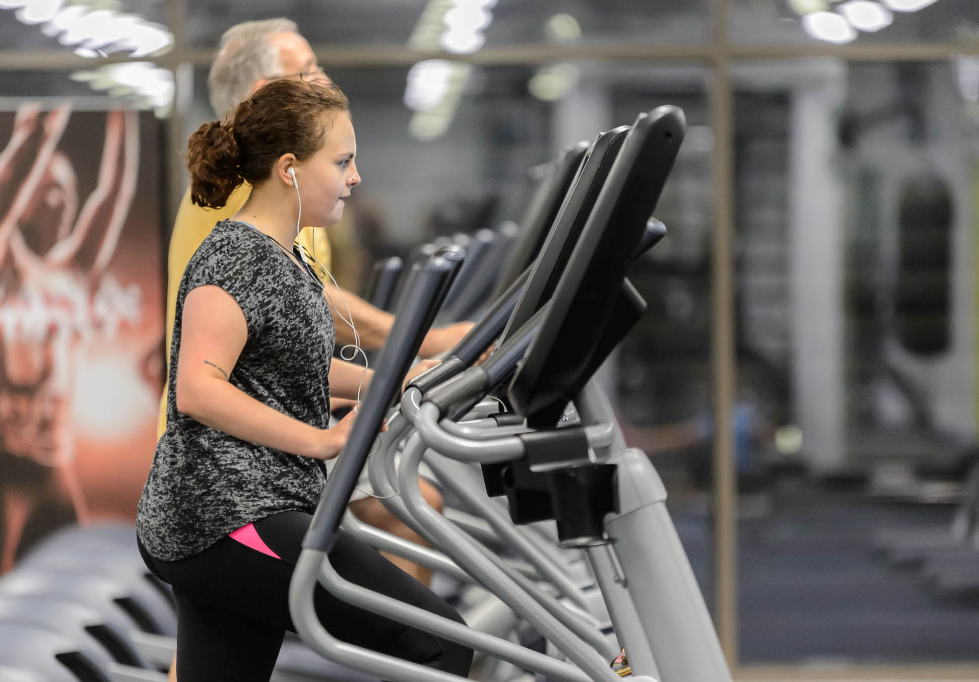 A young woman watches a screen as she used a crossfit machine in a gym