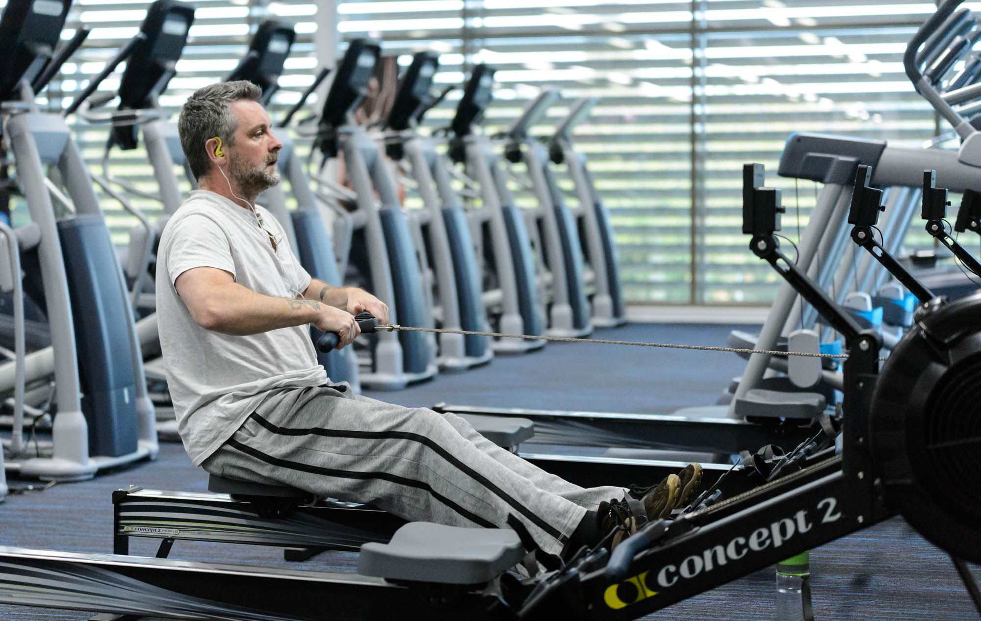 A man using a rowing machine in a gym