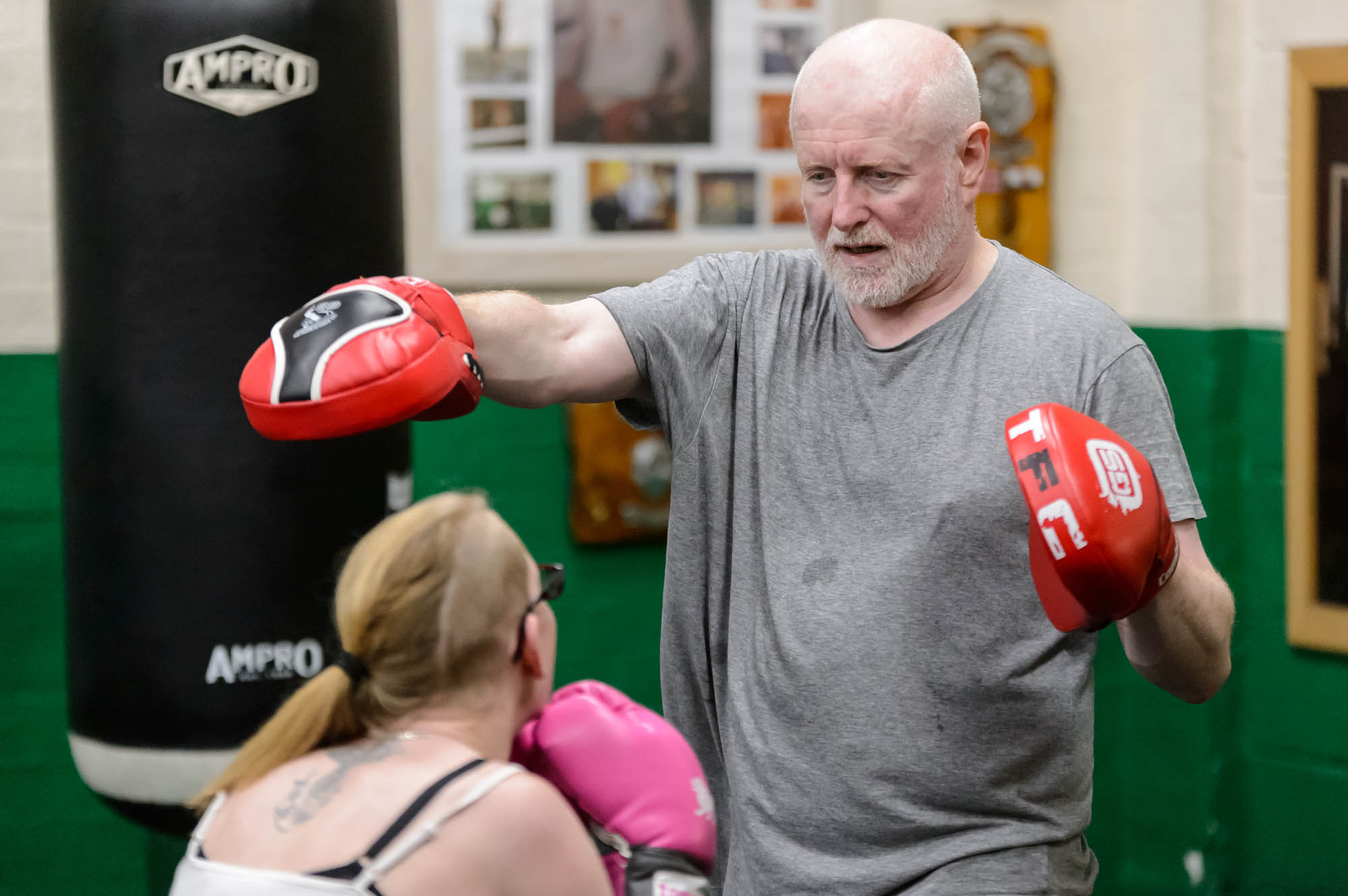 A woman and older man train in boxing together