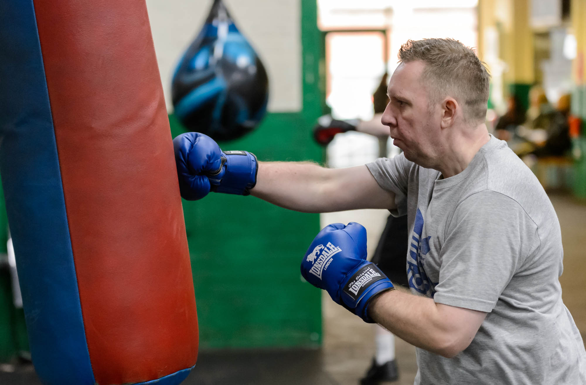 A man punches a punchbag in boxing training