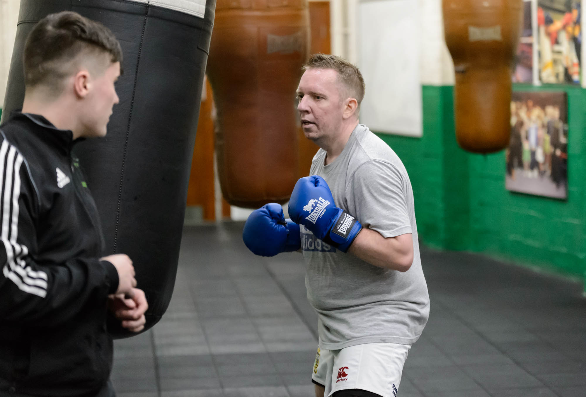 A coach trains a man in boxing