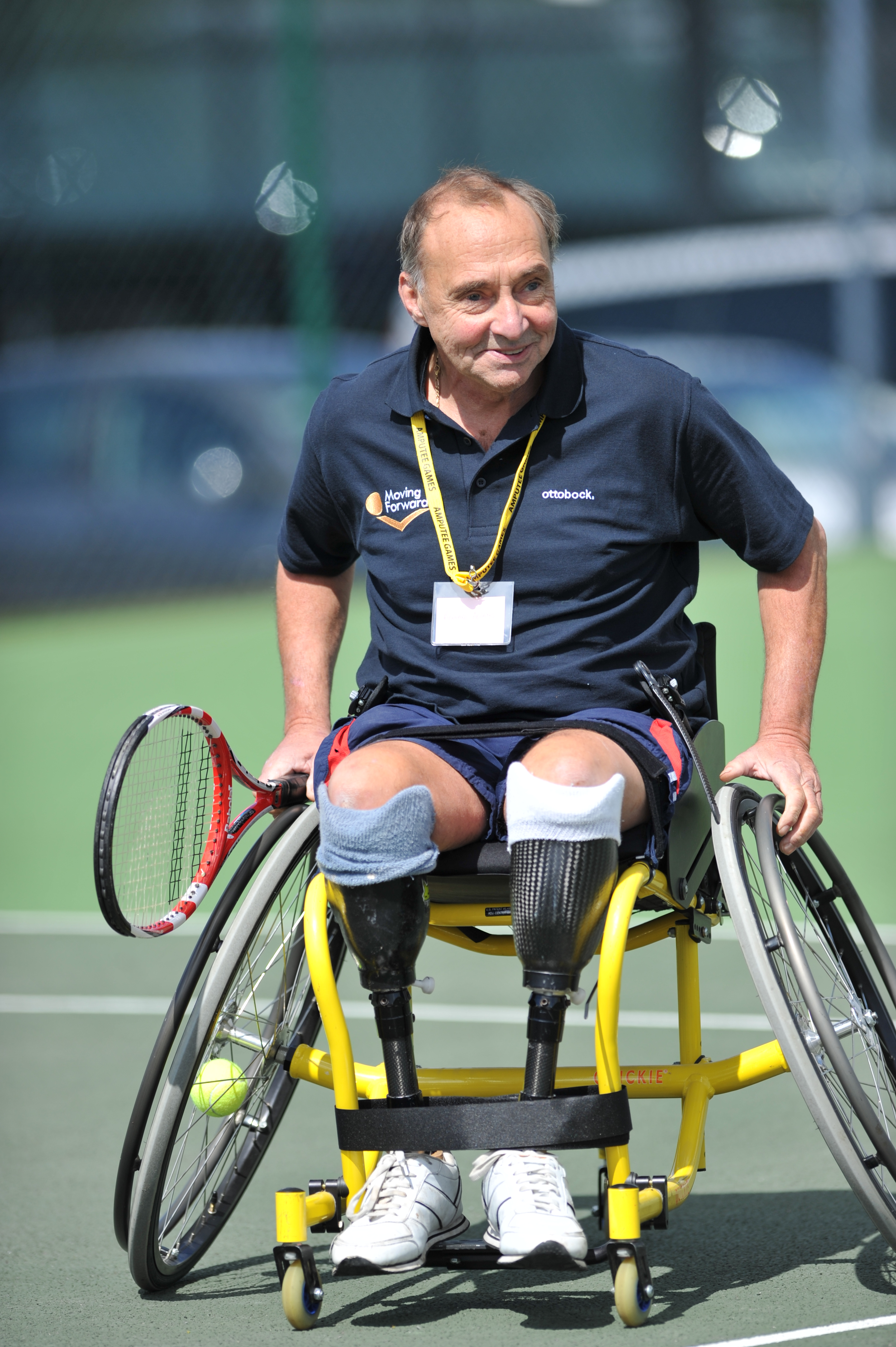 man double amputee in wheelchair playing tennis