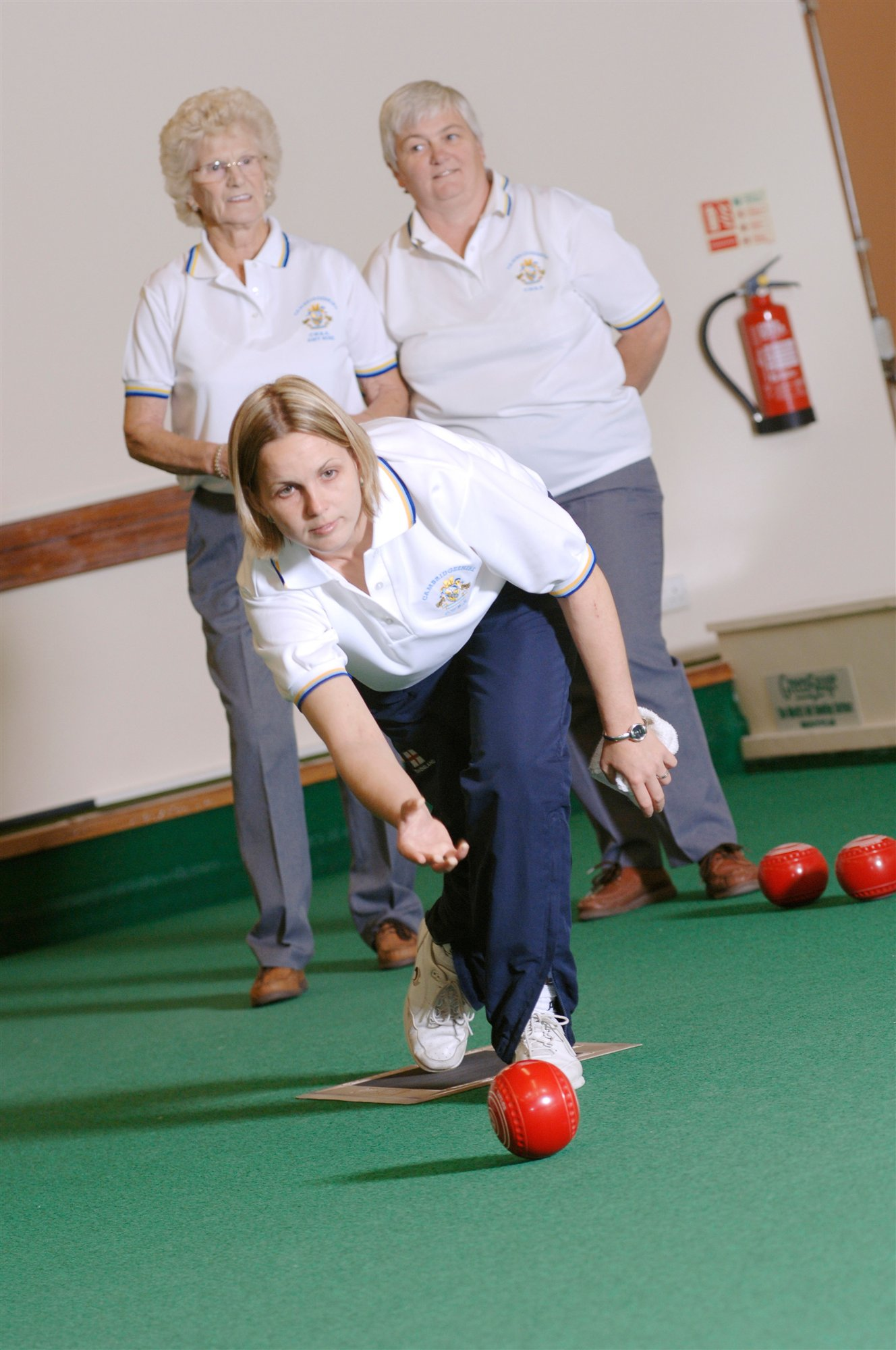 woman bowling a ball indoor bowls watched by two others