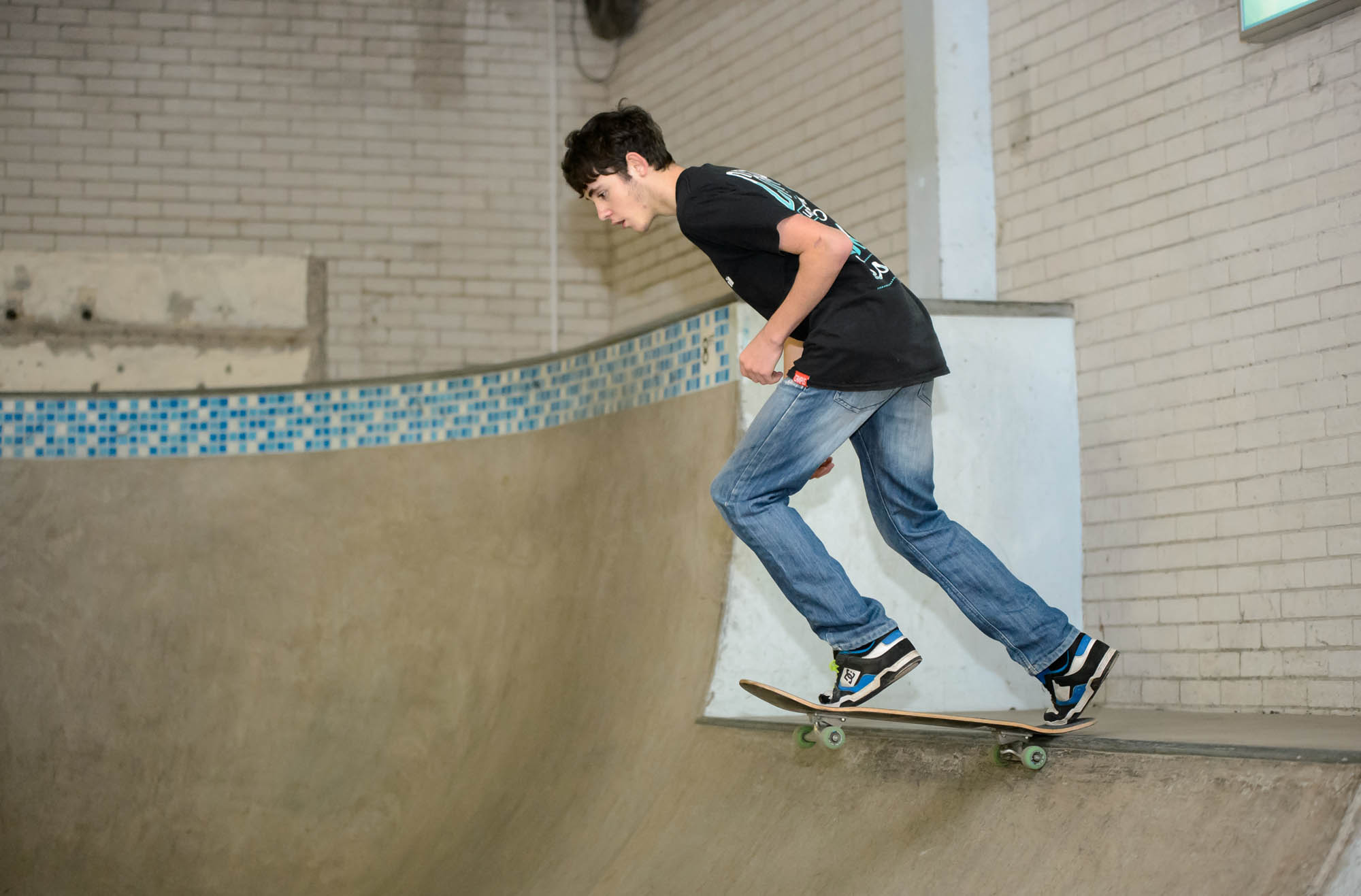A young man skates down into a skatepark