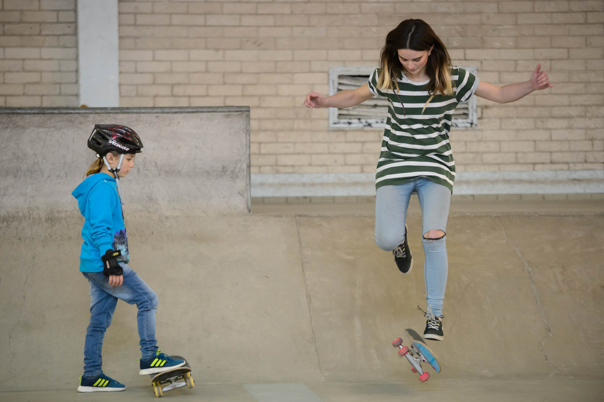 An older teenage girl practices skateboarding tricks next to a younger girl