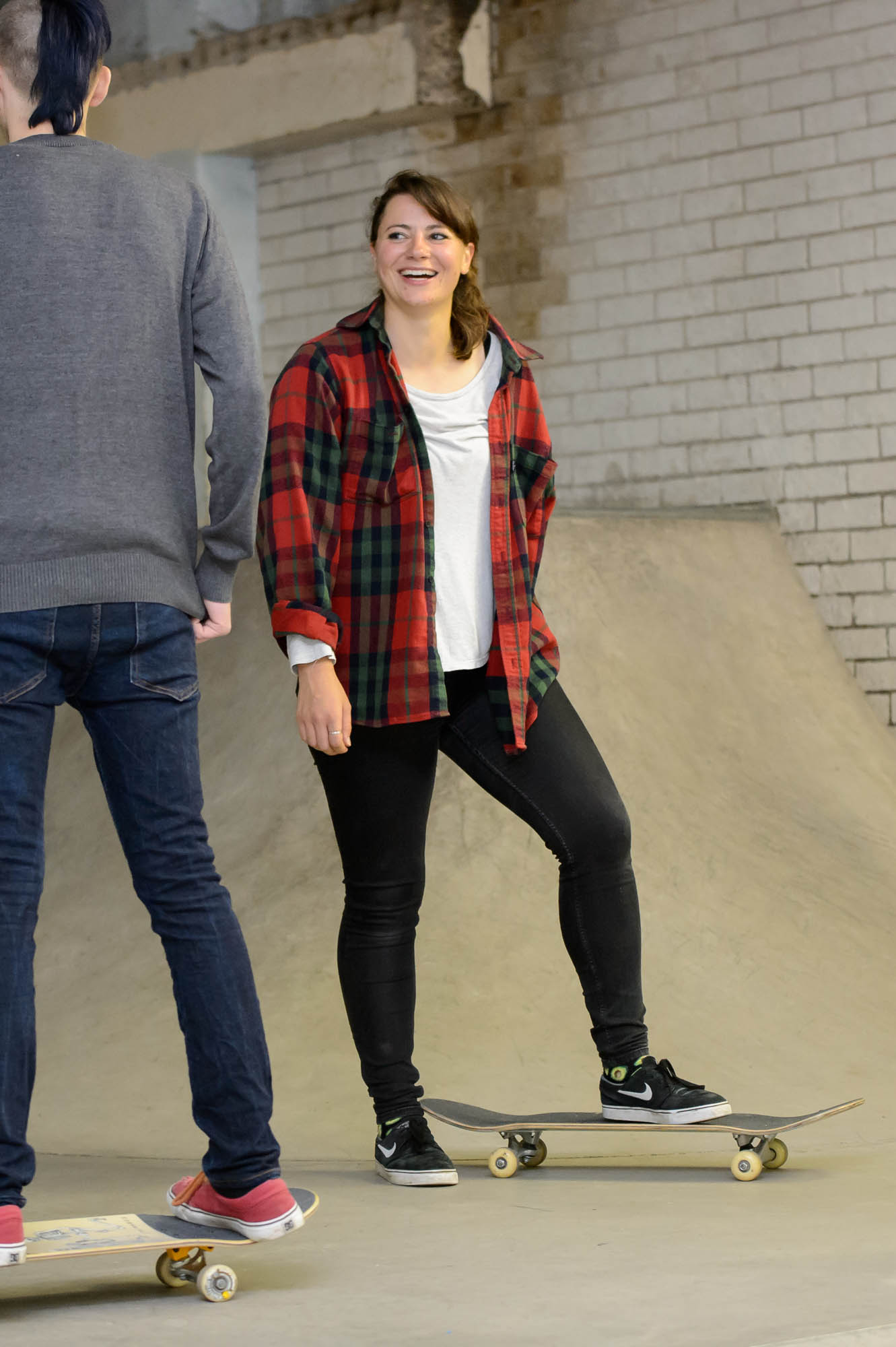 A young woman standing on a skateboard