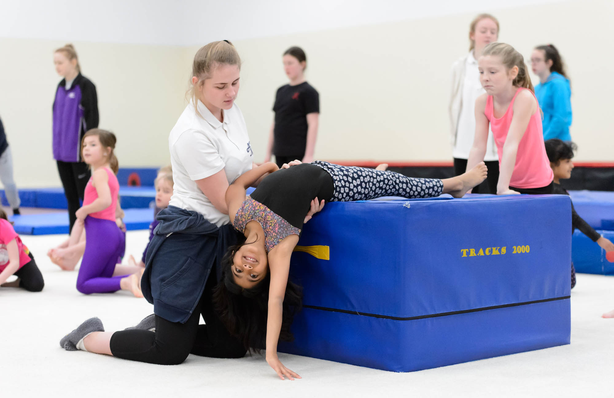 A young adult coach helps a child train in gymnastics