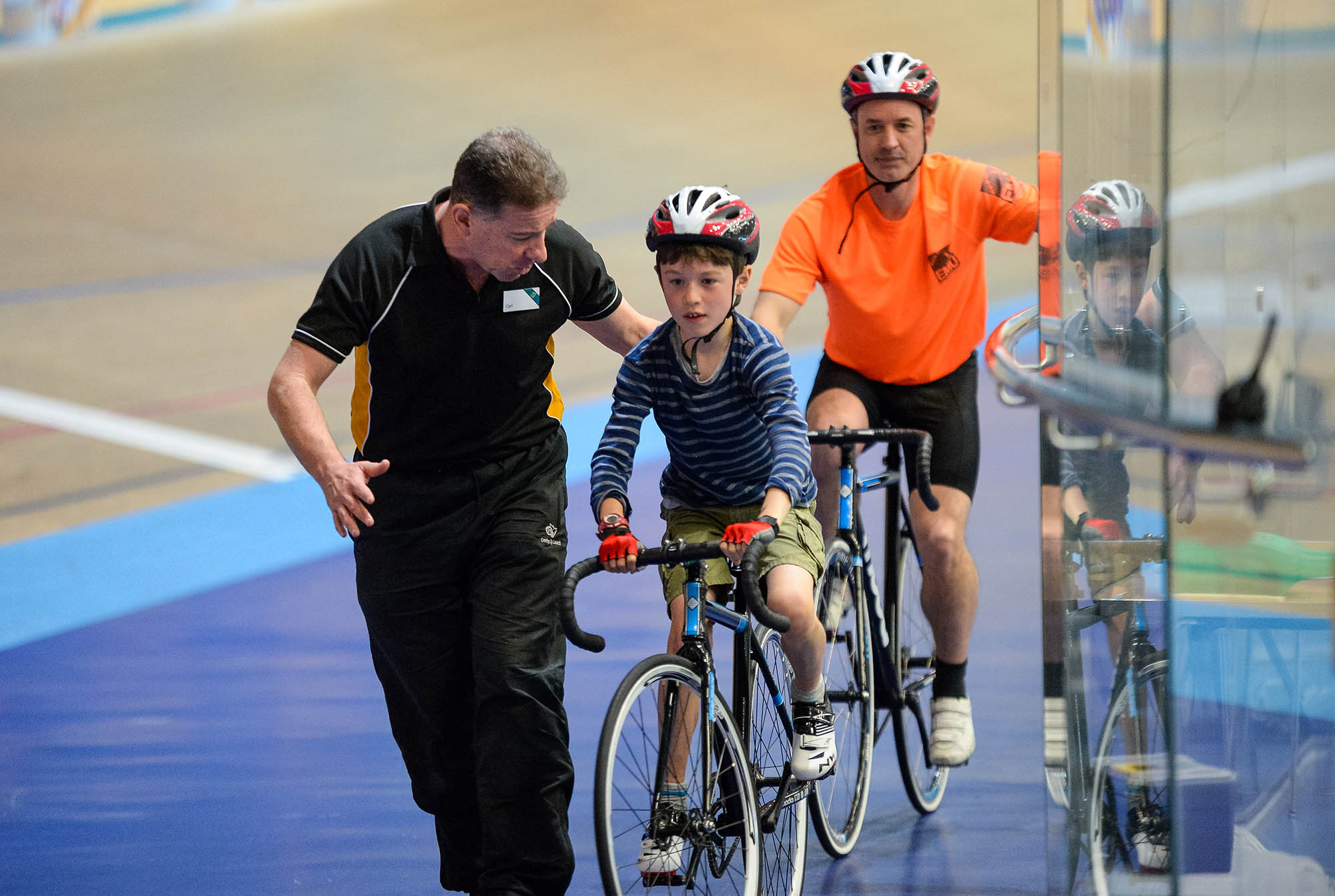 boy on bike being supported by coach indoors cycling