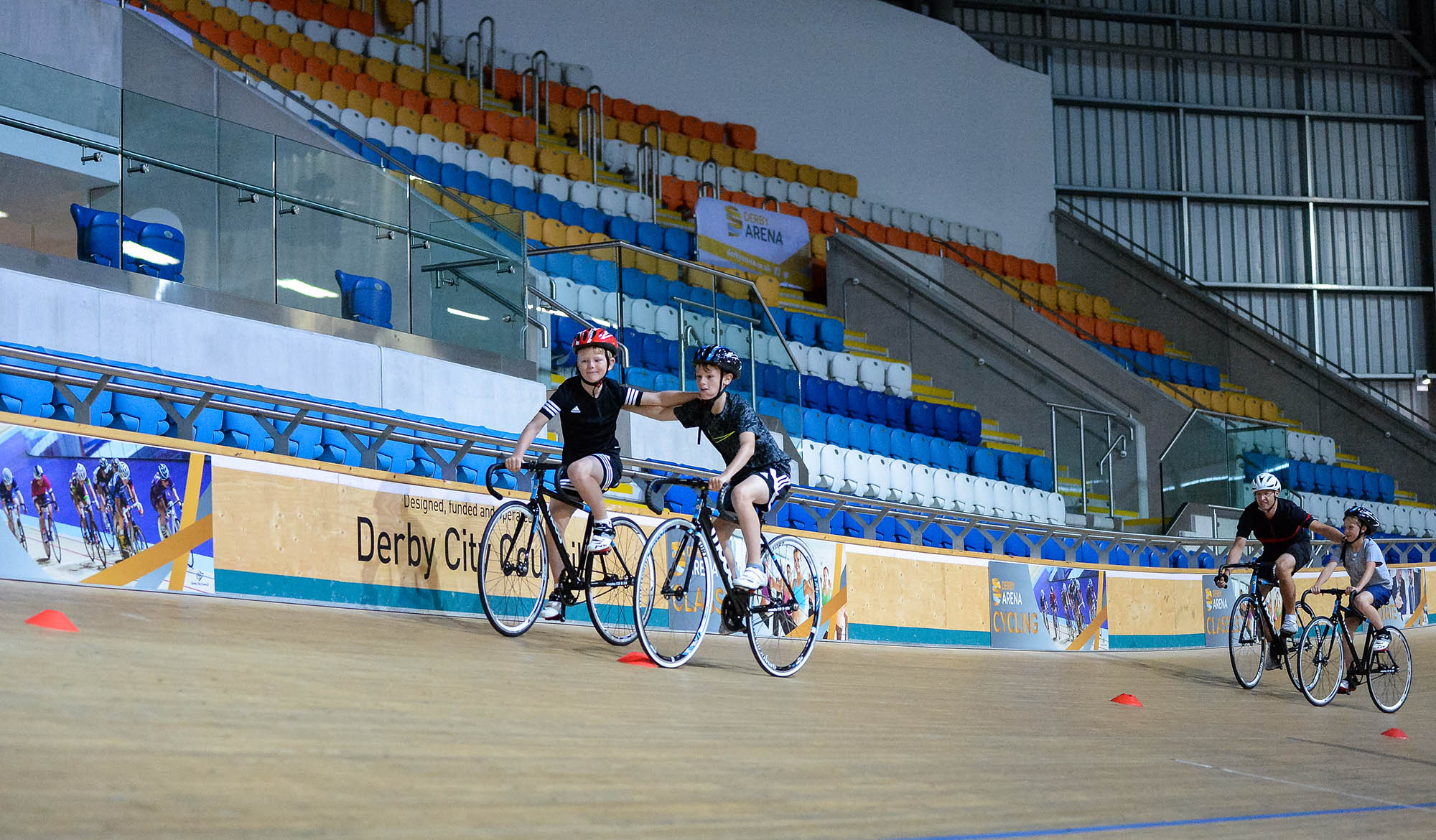 two boys holding each other up for balance on bikes in velodrome