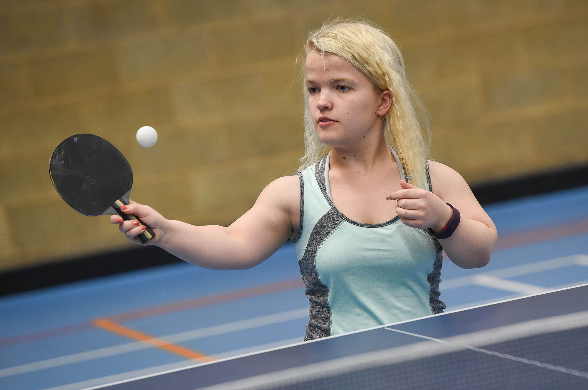 woman with eye on ball playing table tennis