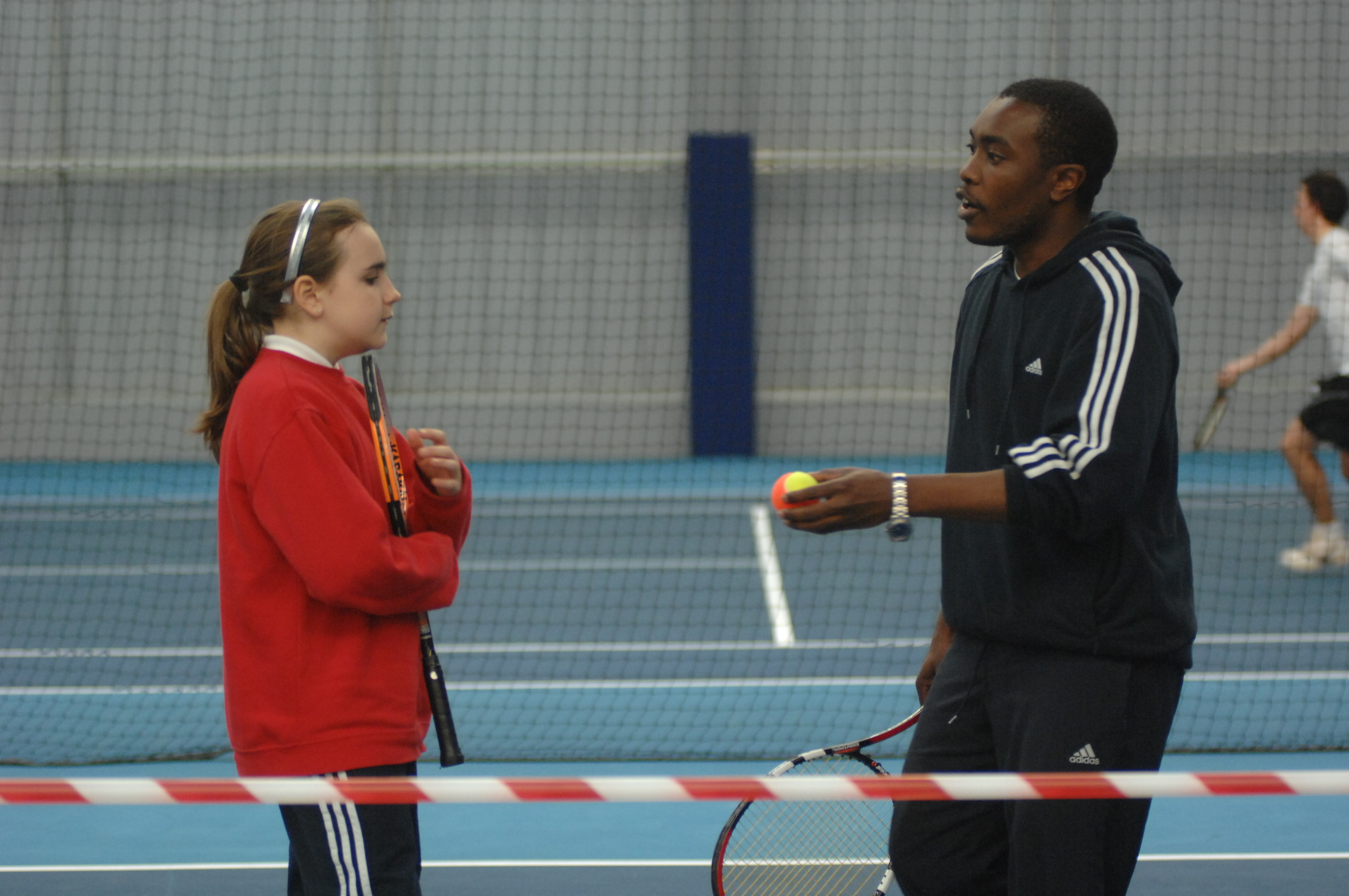 male instructor talking to girl with tennis racket