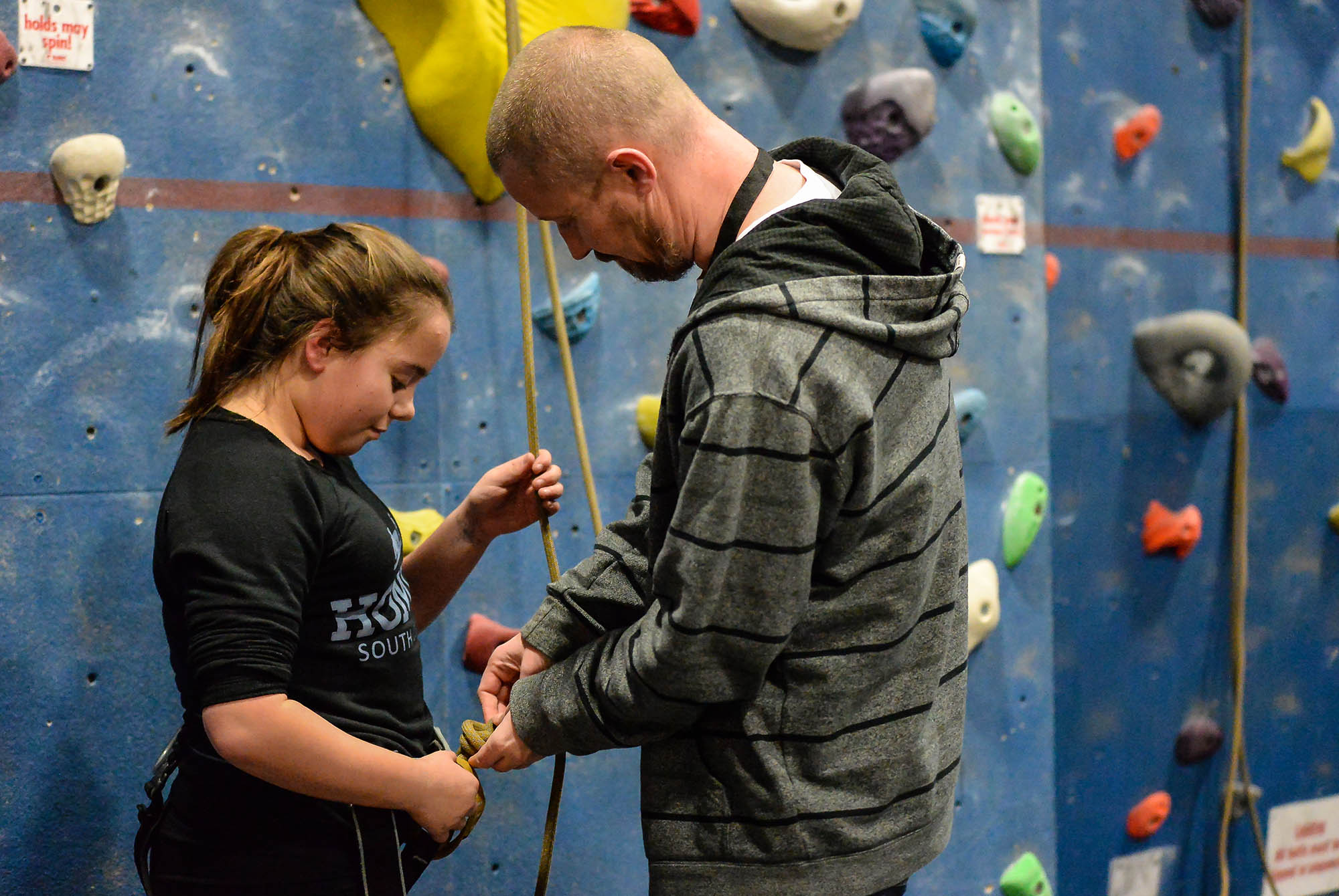 man instructor helping girl into climbing harness