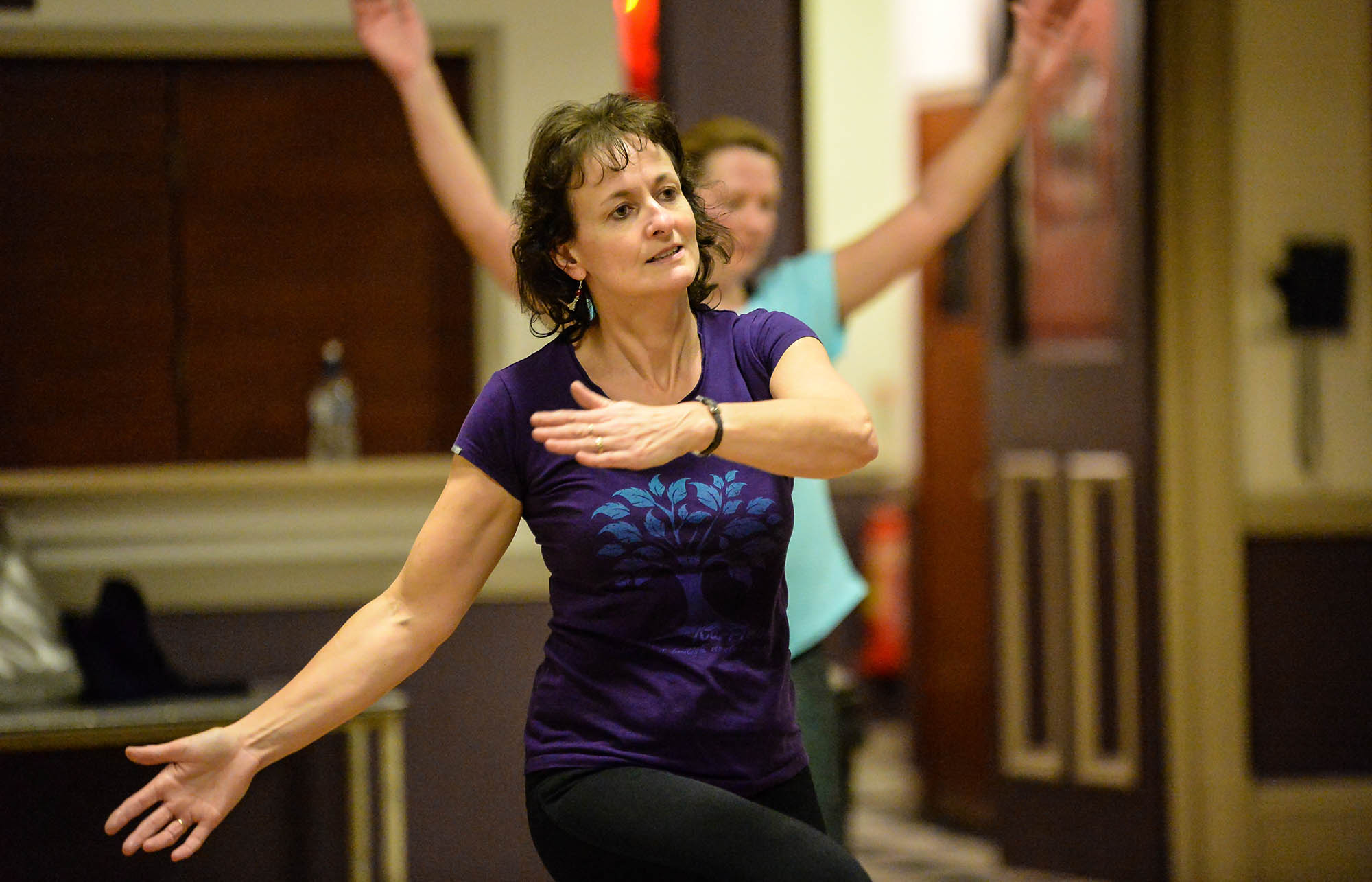 woman looking ahead with arms across body doing exercise indoors