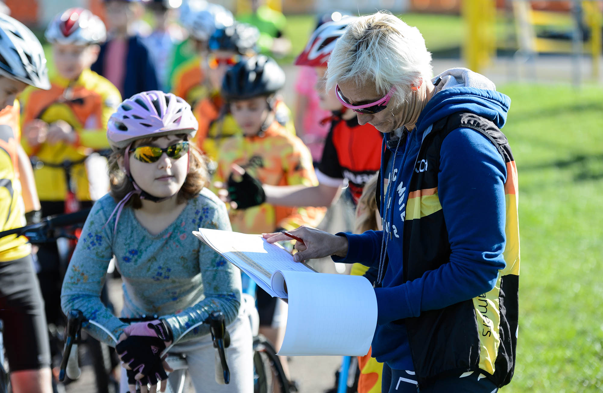A female cycling coach with the children she is coaching