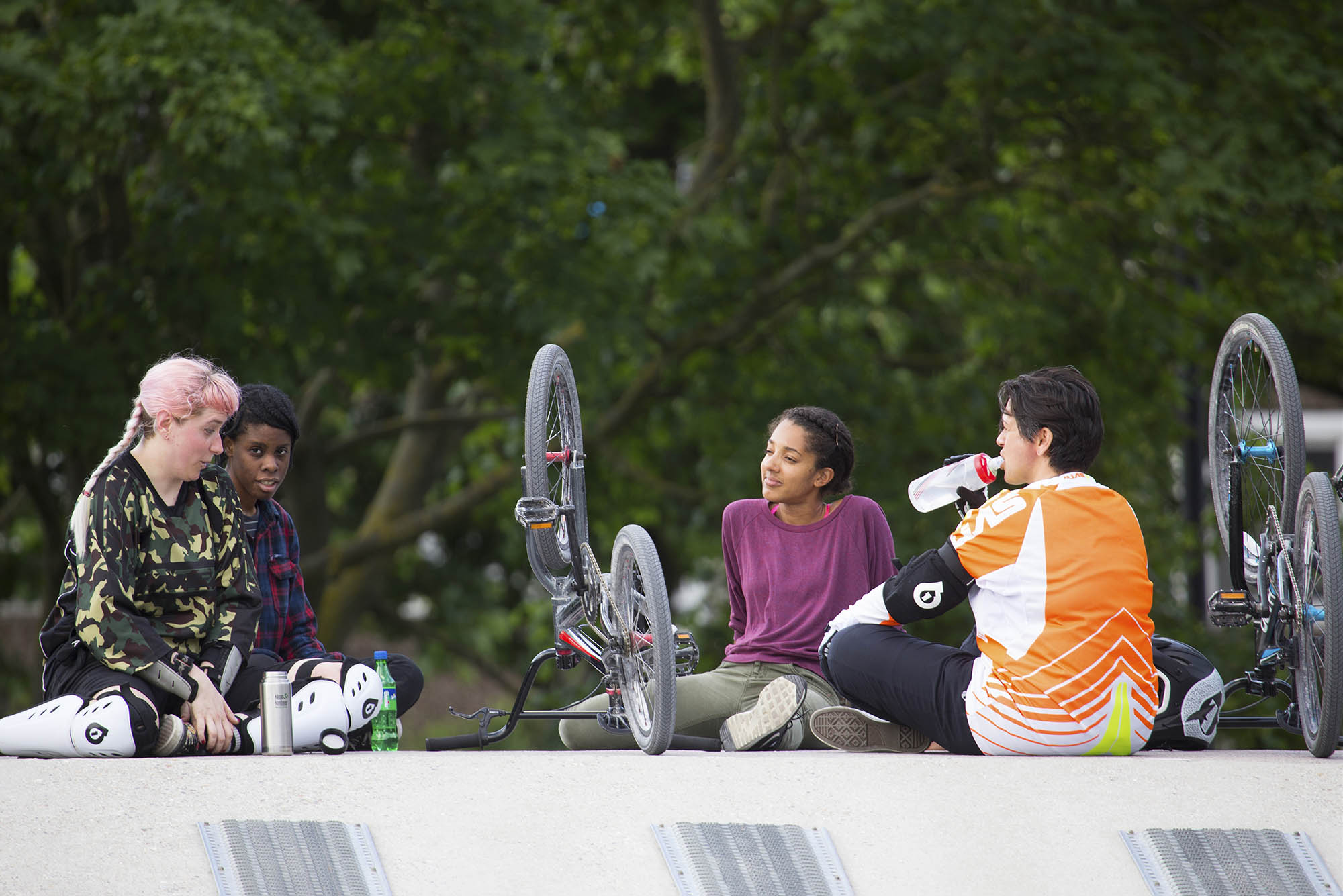 four people sat down and taking a breather during bmx riding