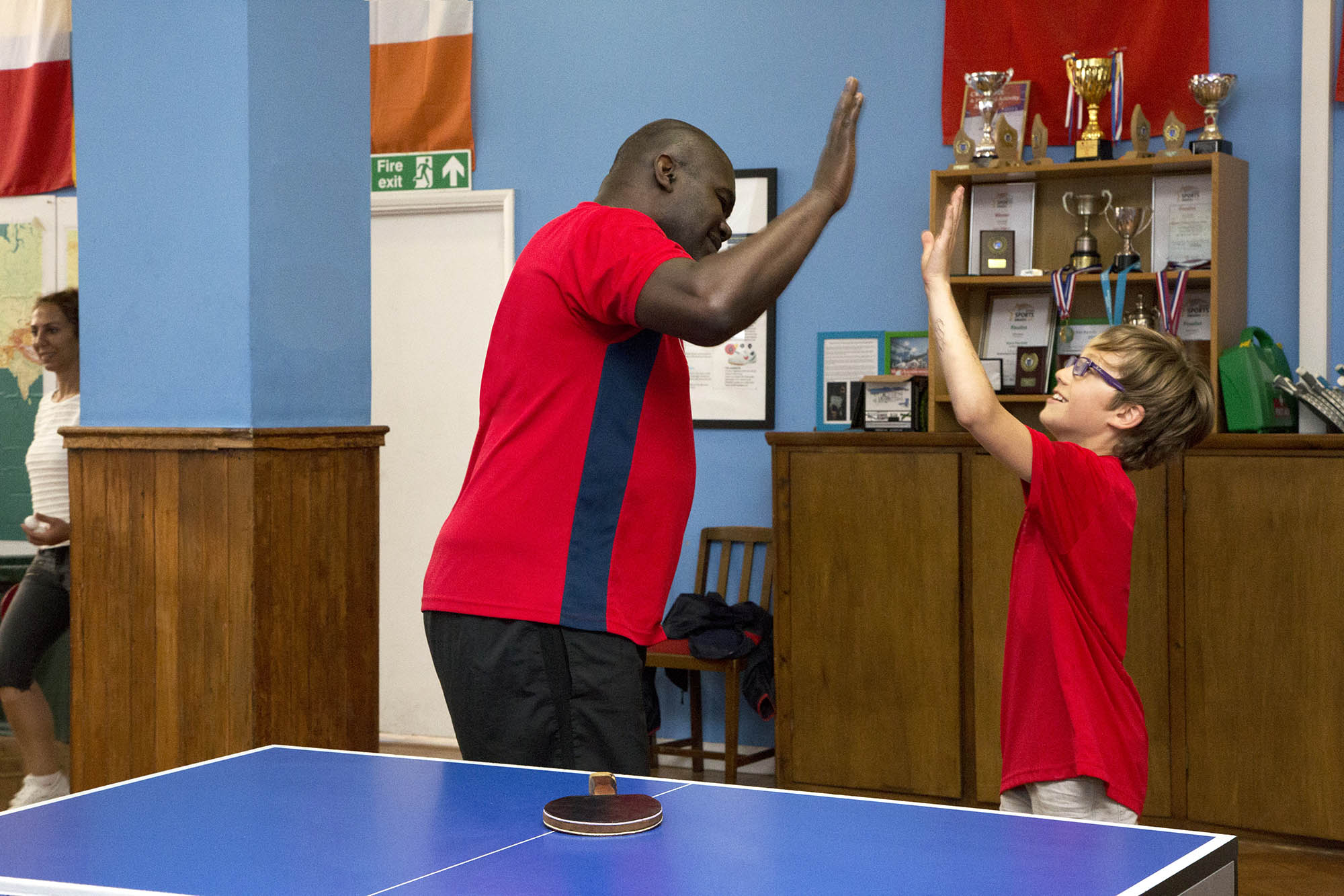 man high-fiving younger boy at table tennis table