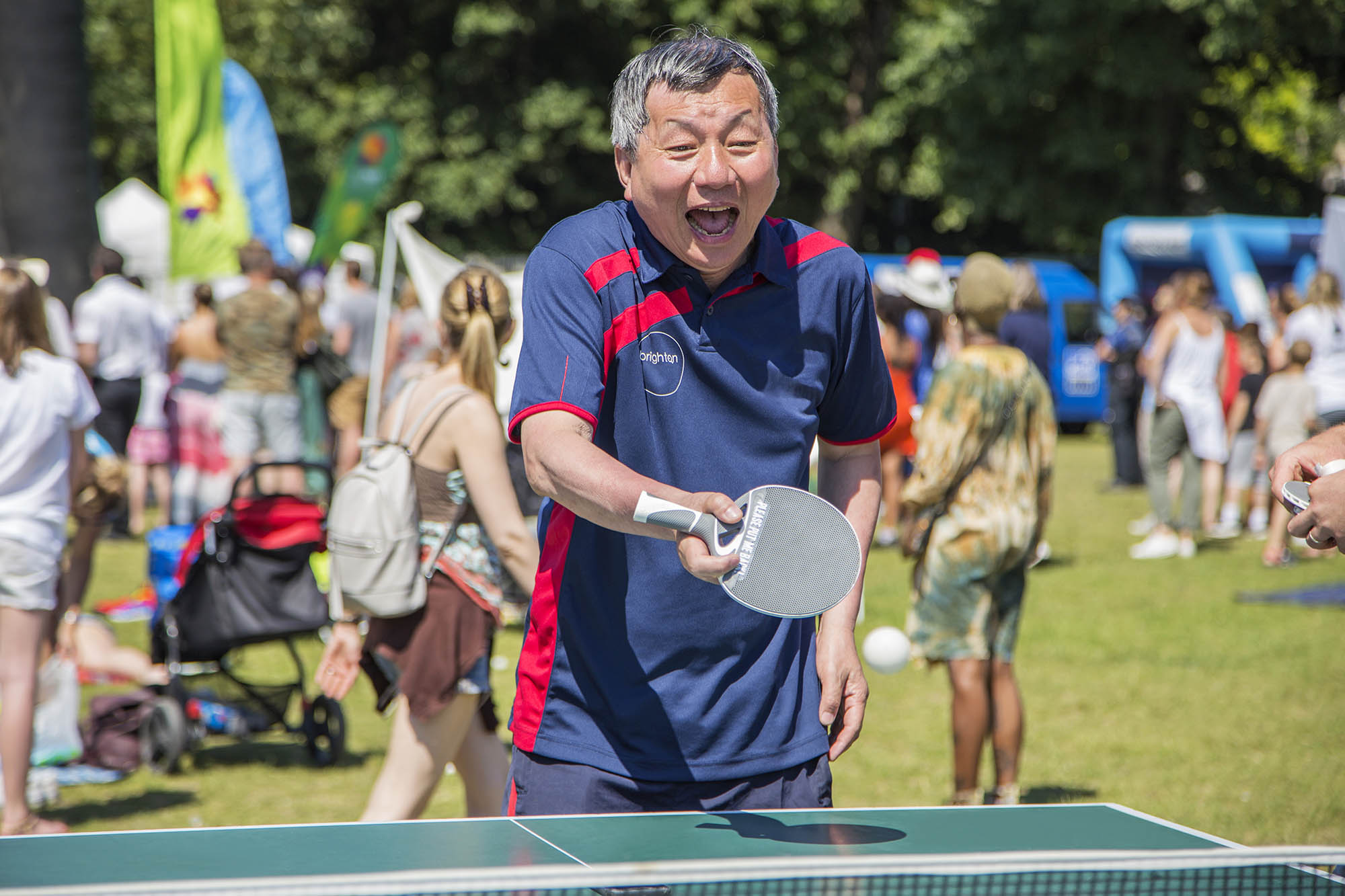 smiling man playing table tennis outdoors