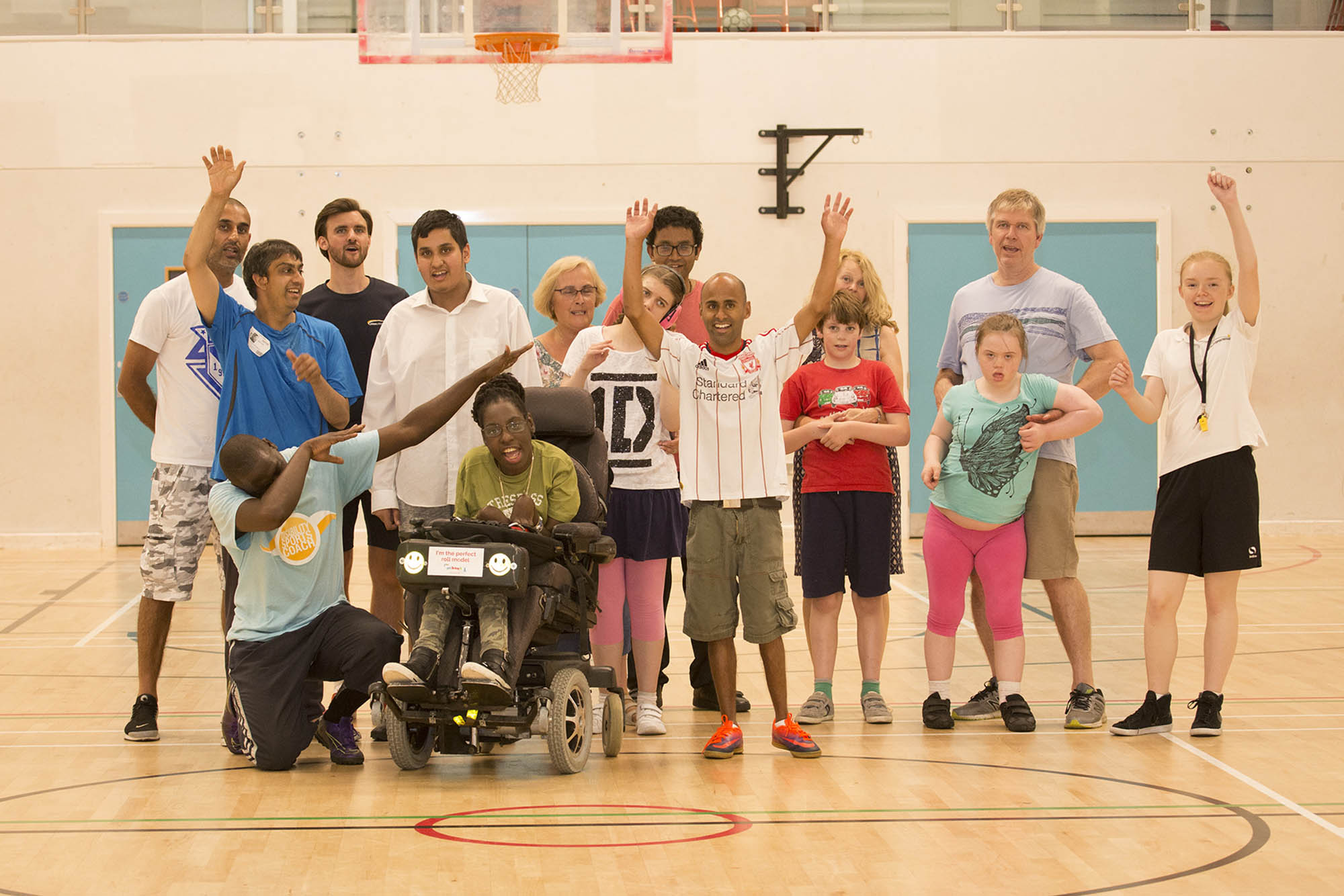 group of people all ages disabled and non-disabled in sports hall group photo