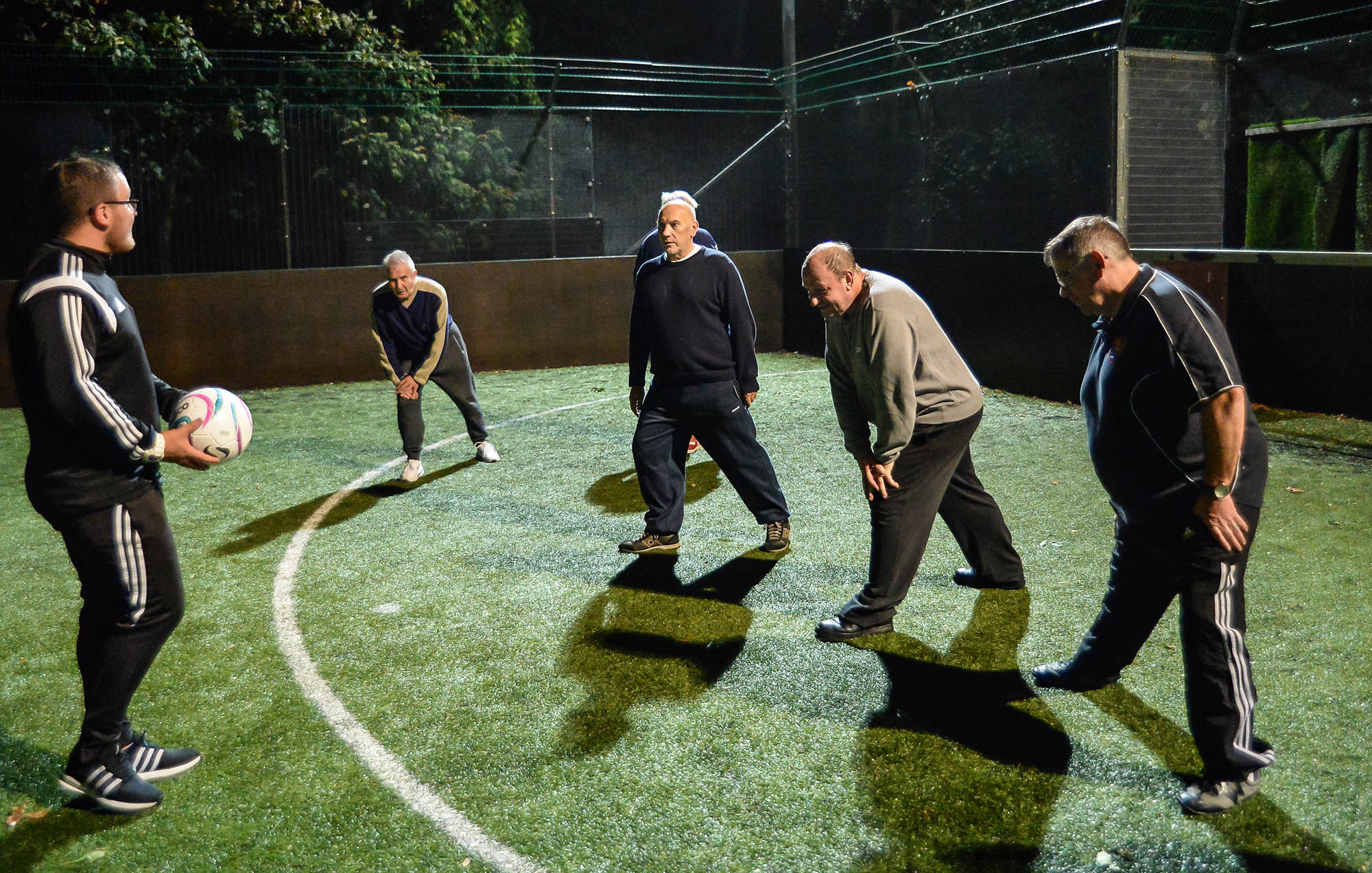 group of older men stretching before walking football