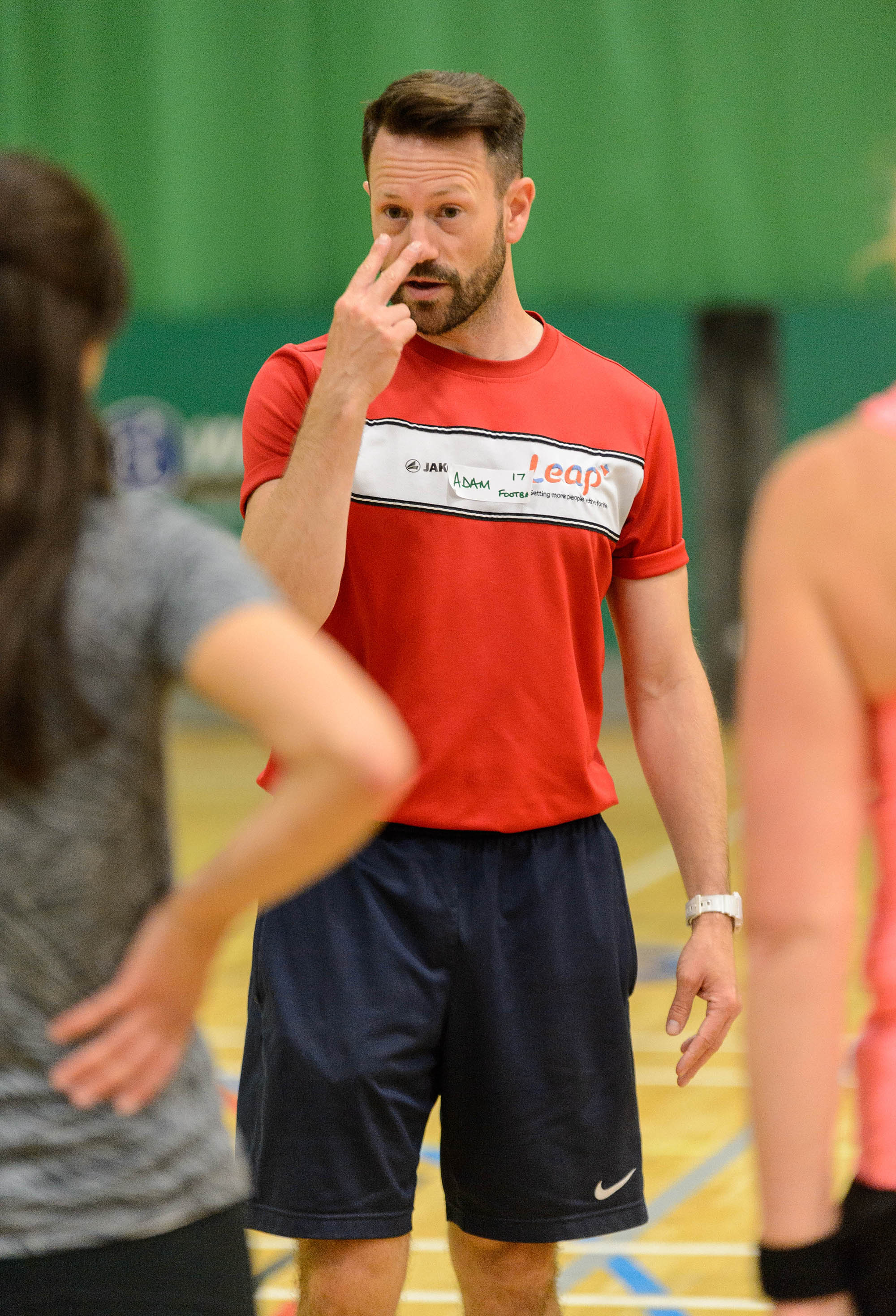 man coach pointing at own eyes