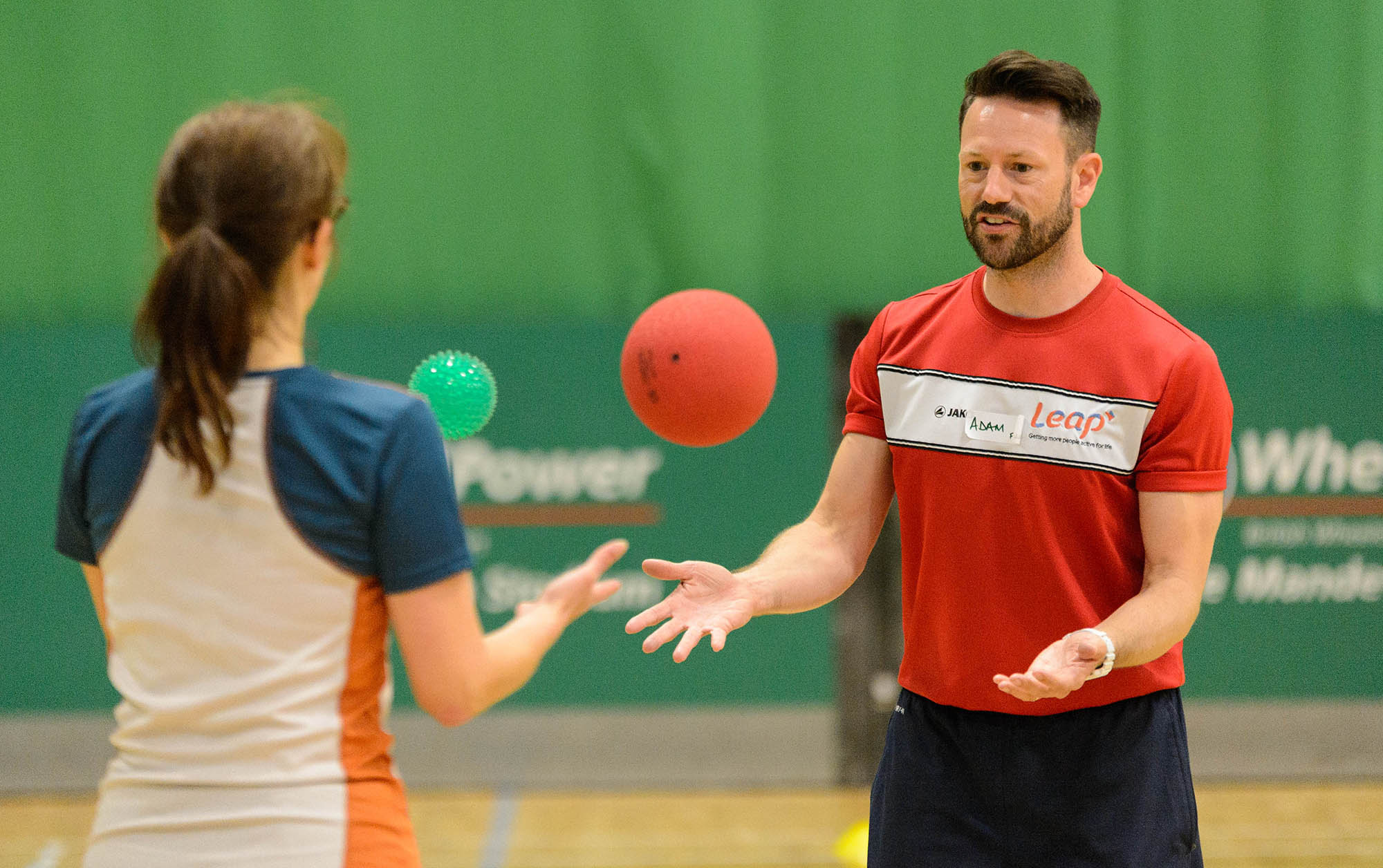 male coach and woman throwing balls to each other