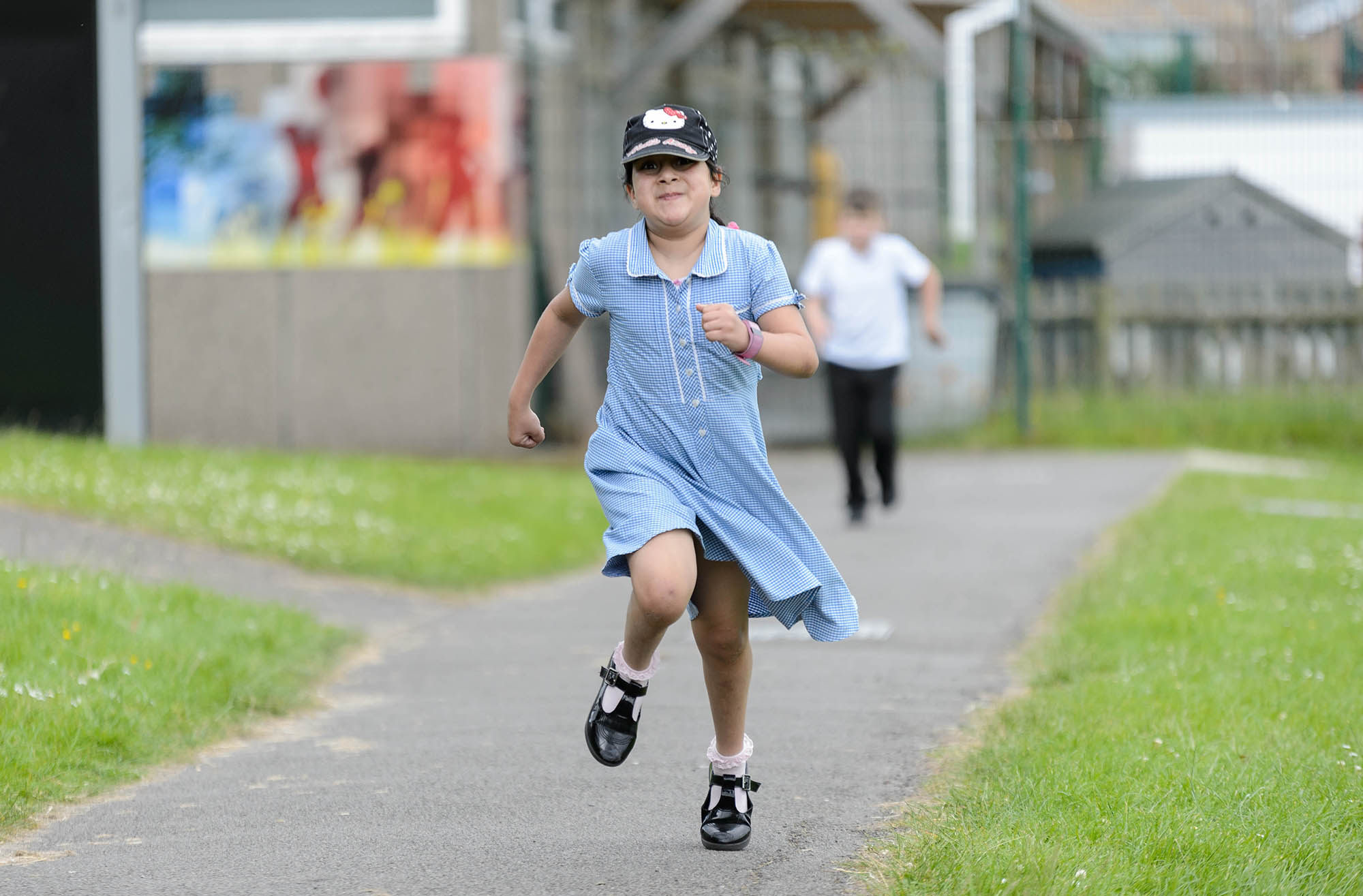 girl running down a path in cap and school uniform