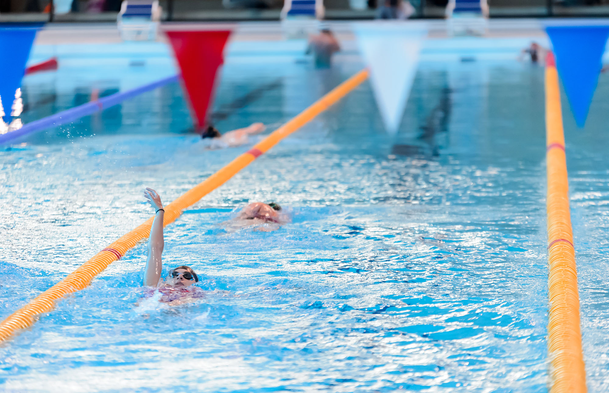 A woman swims backstroke in a lane at the London Aquatics Centre