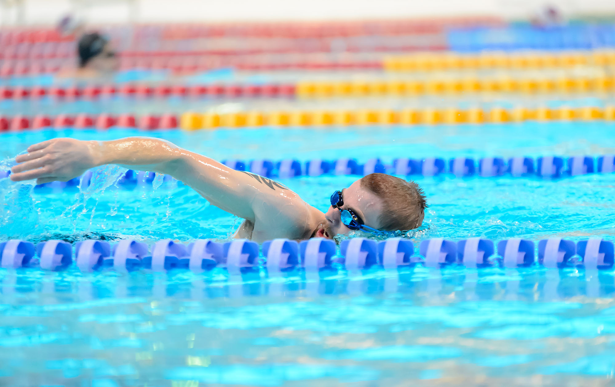 A man swims freestyle in a lane at London Aquatics Centre