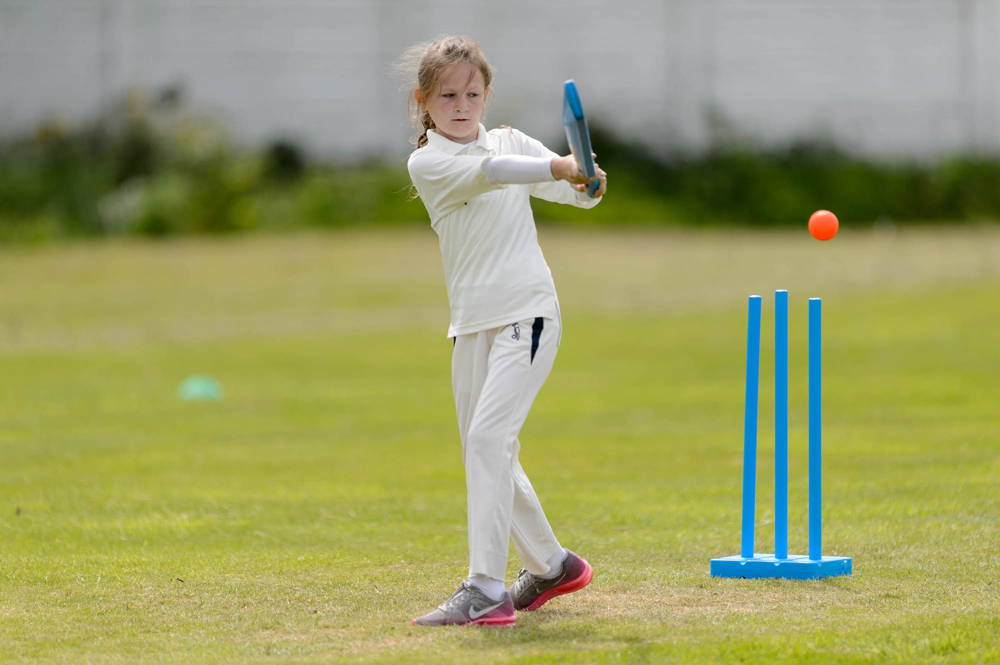 young girl batting a ball away cricket outdoors