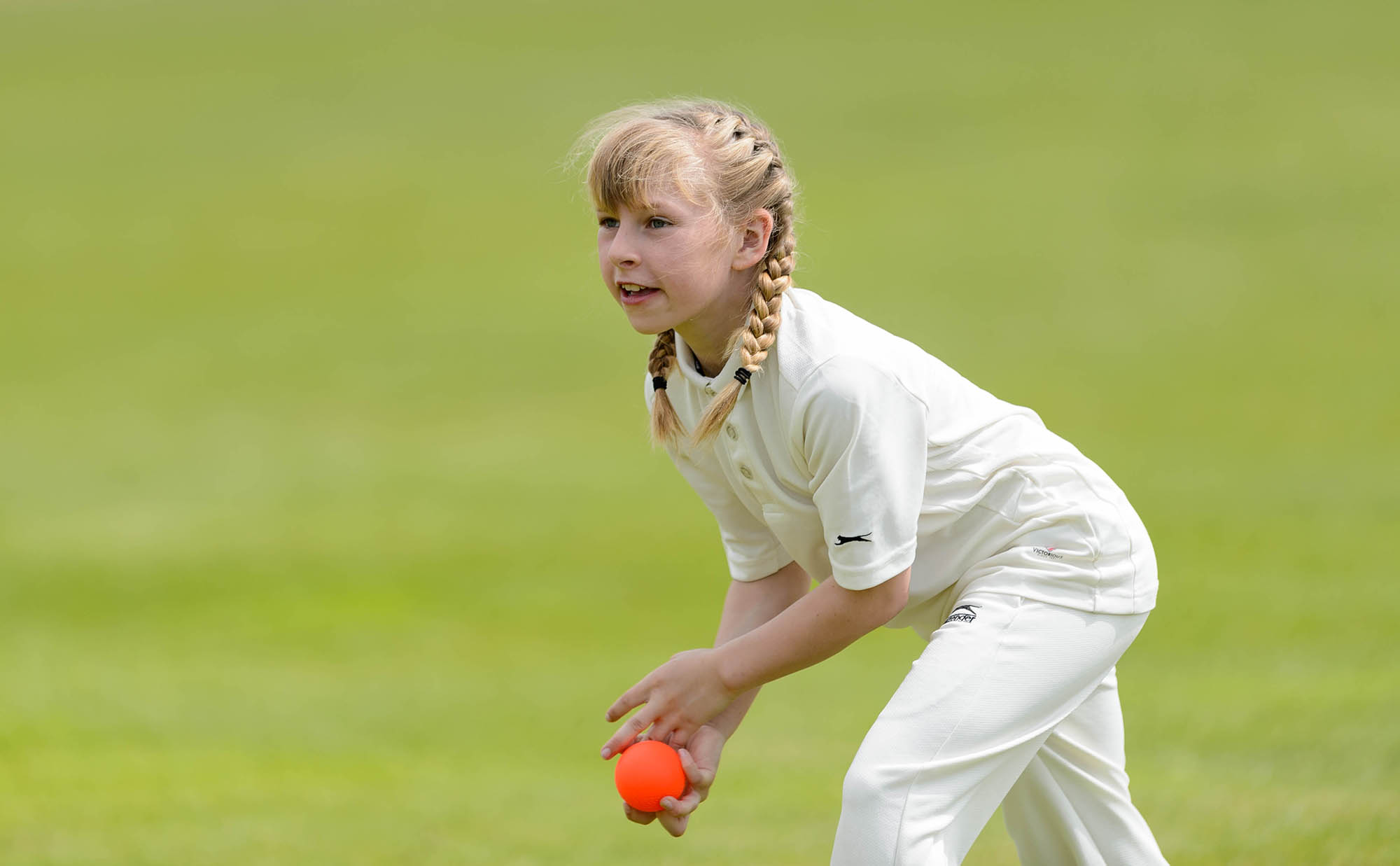 girl in cricket whites with ball in hand
