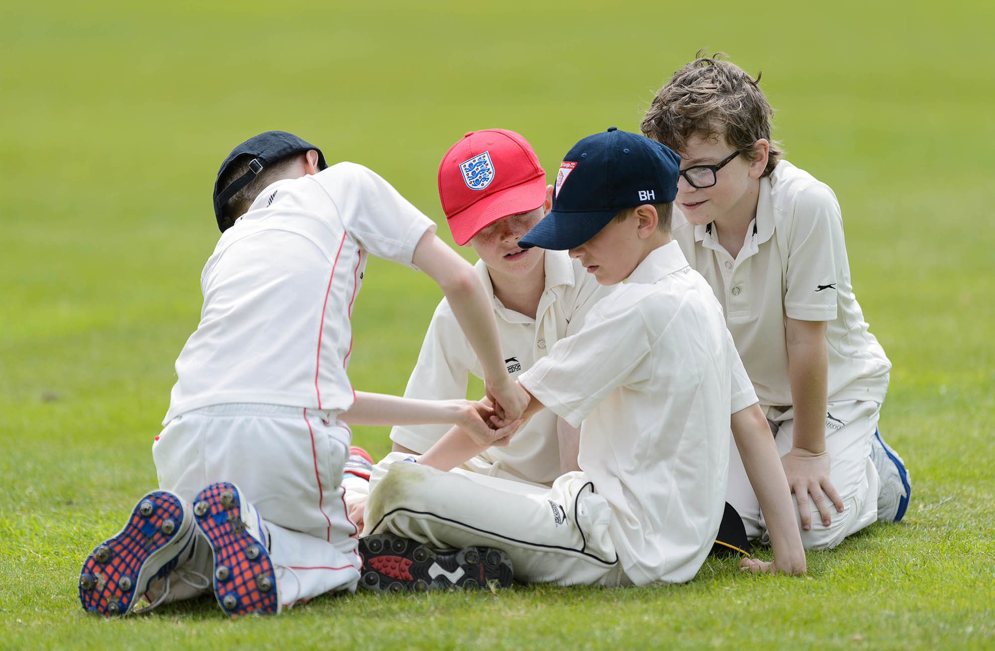 four boys in cricket whites sat on grass