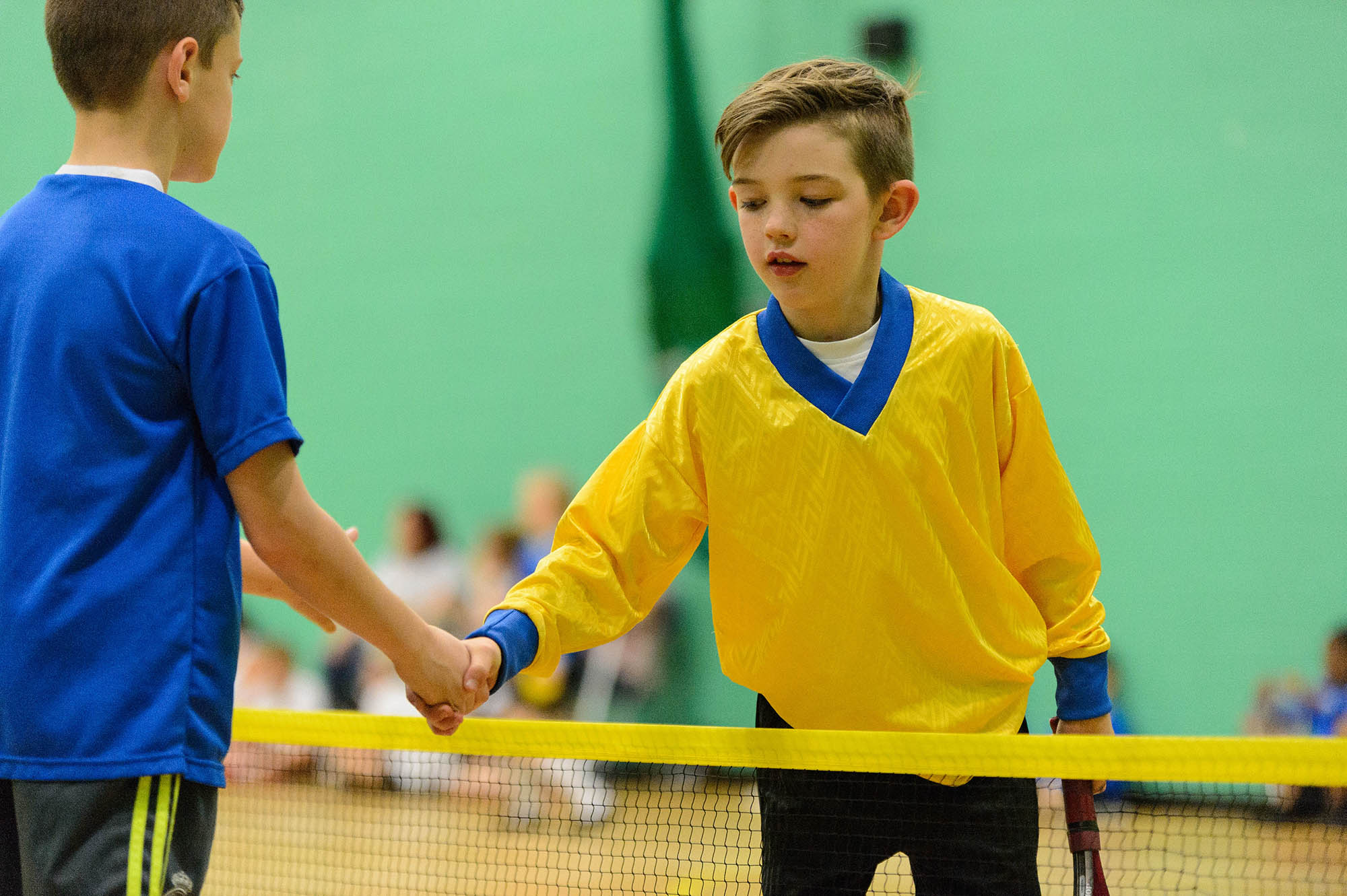 two boys shaking hands at the tennis net