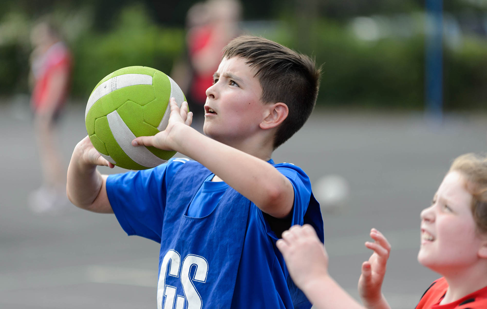 boy playing netball with ball looking up about to shoot
