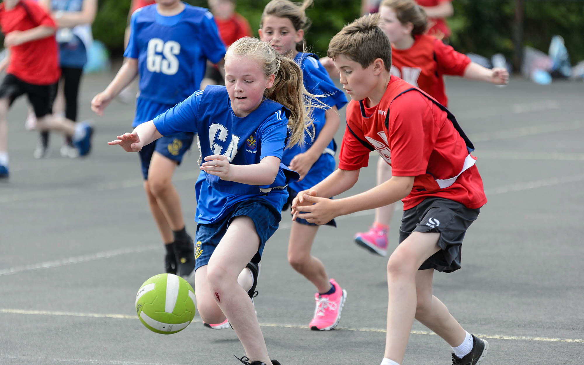 boy and girl chasing after the ball playing netball