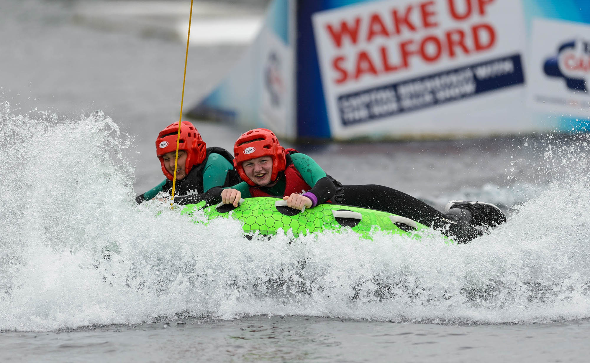 two girls on inflatable on water smiling