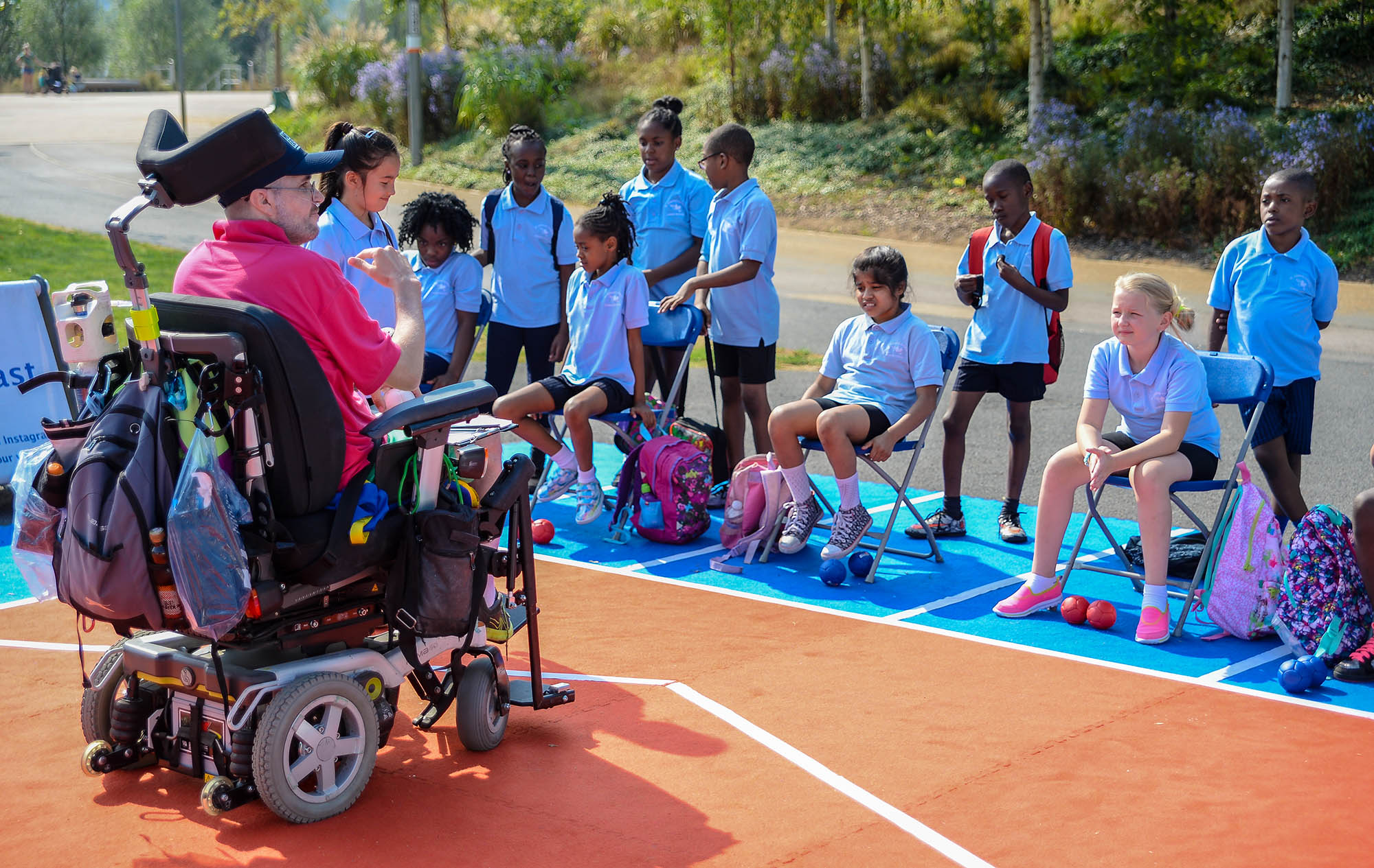 man in wheelchair coaching group of children