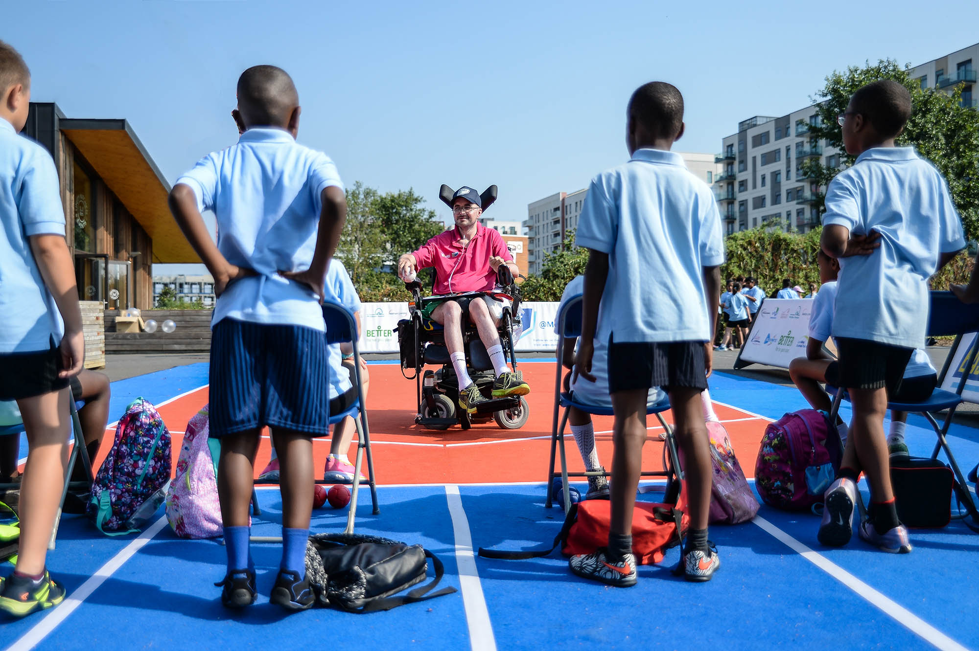 group of boys with man in wheelchair in front coaching