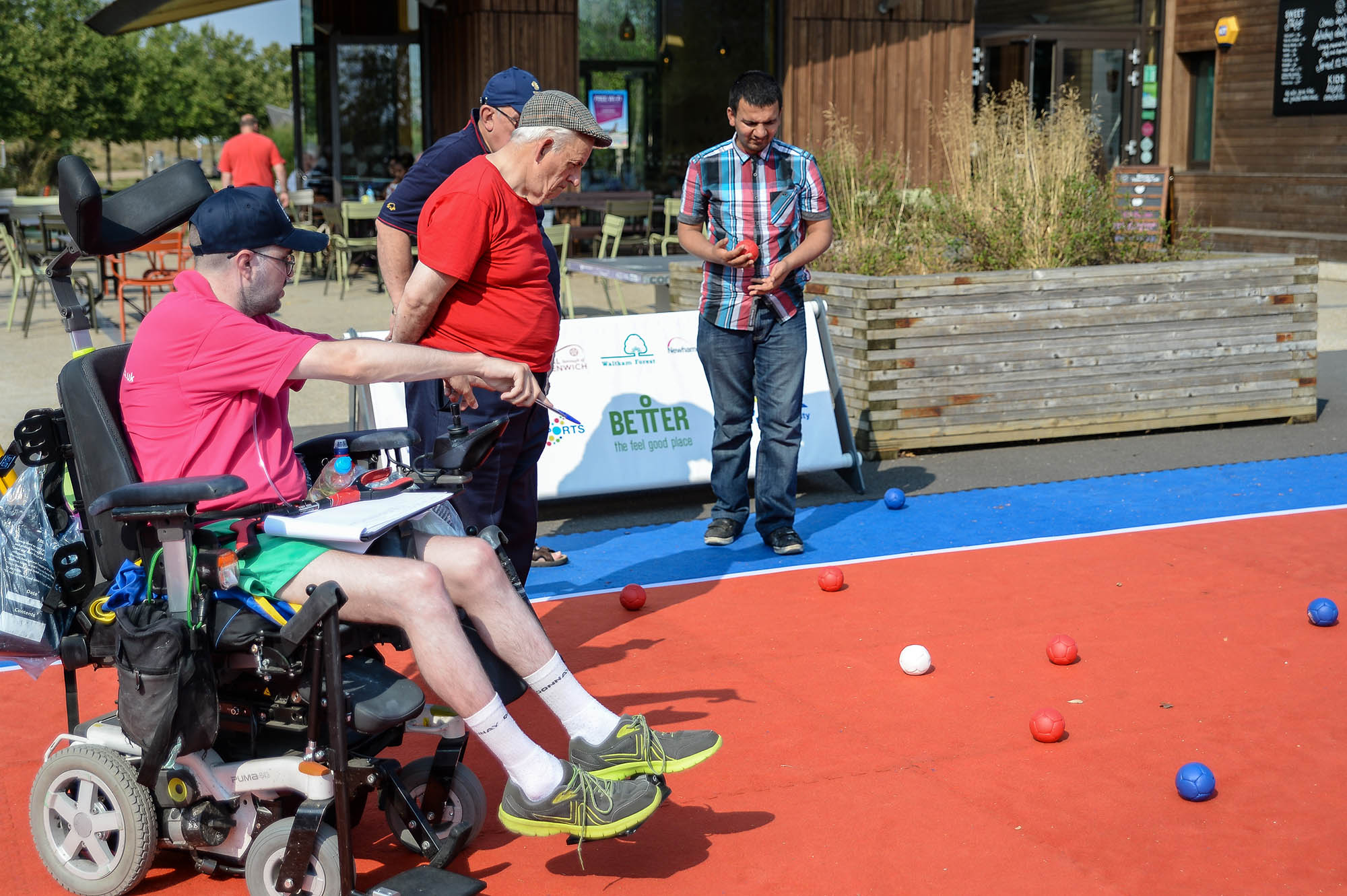 man in wheelchair instructing older man looking at balls