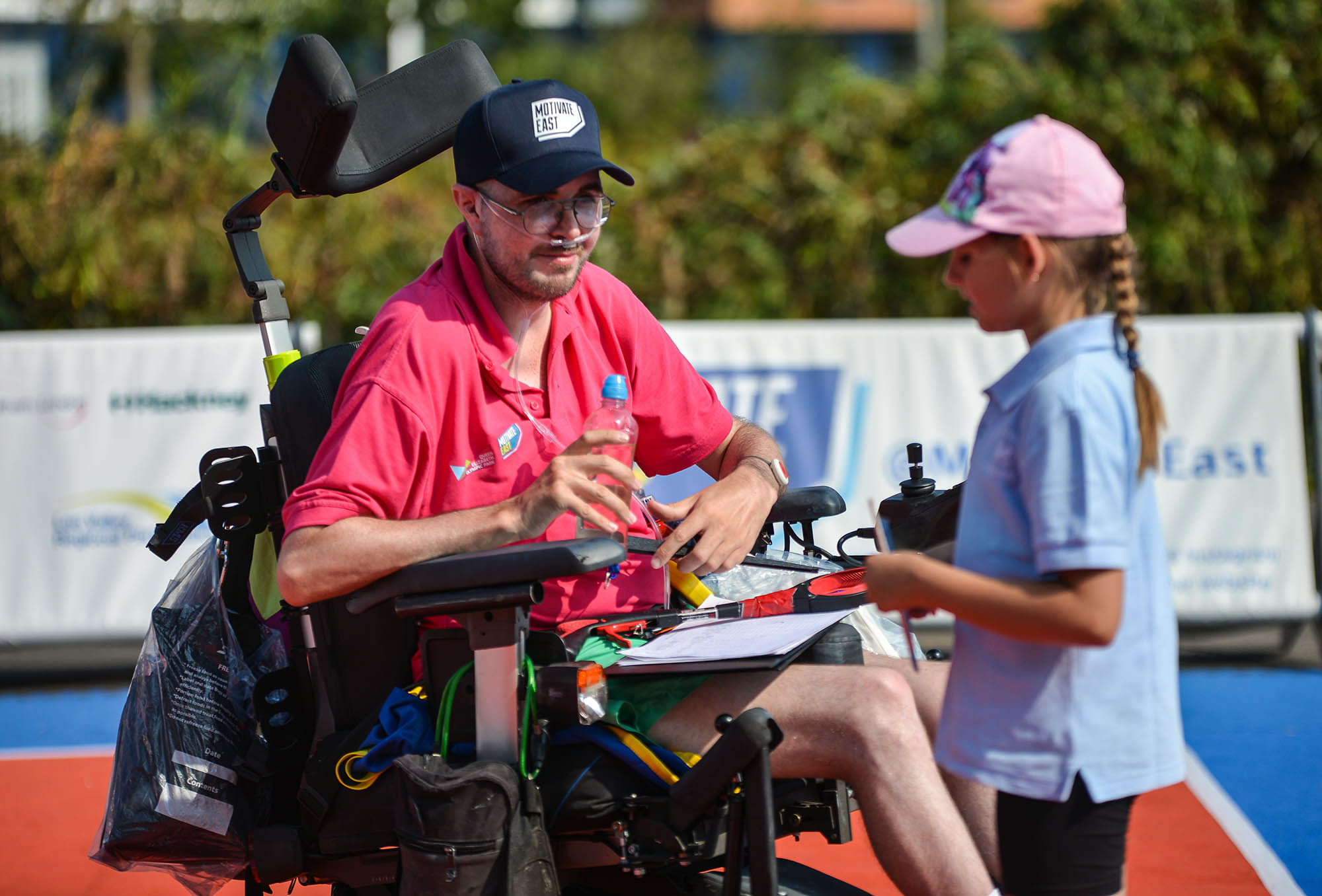 man in wheelchair talking to young girl