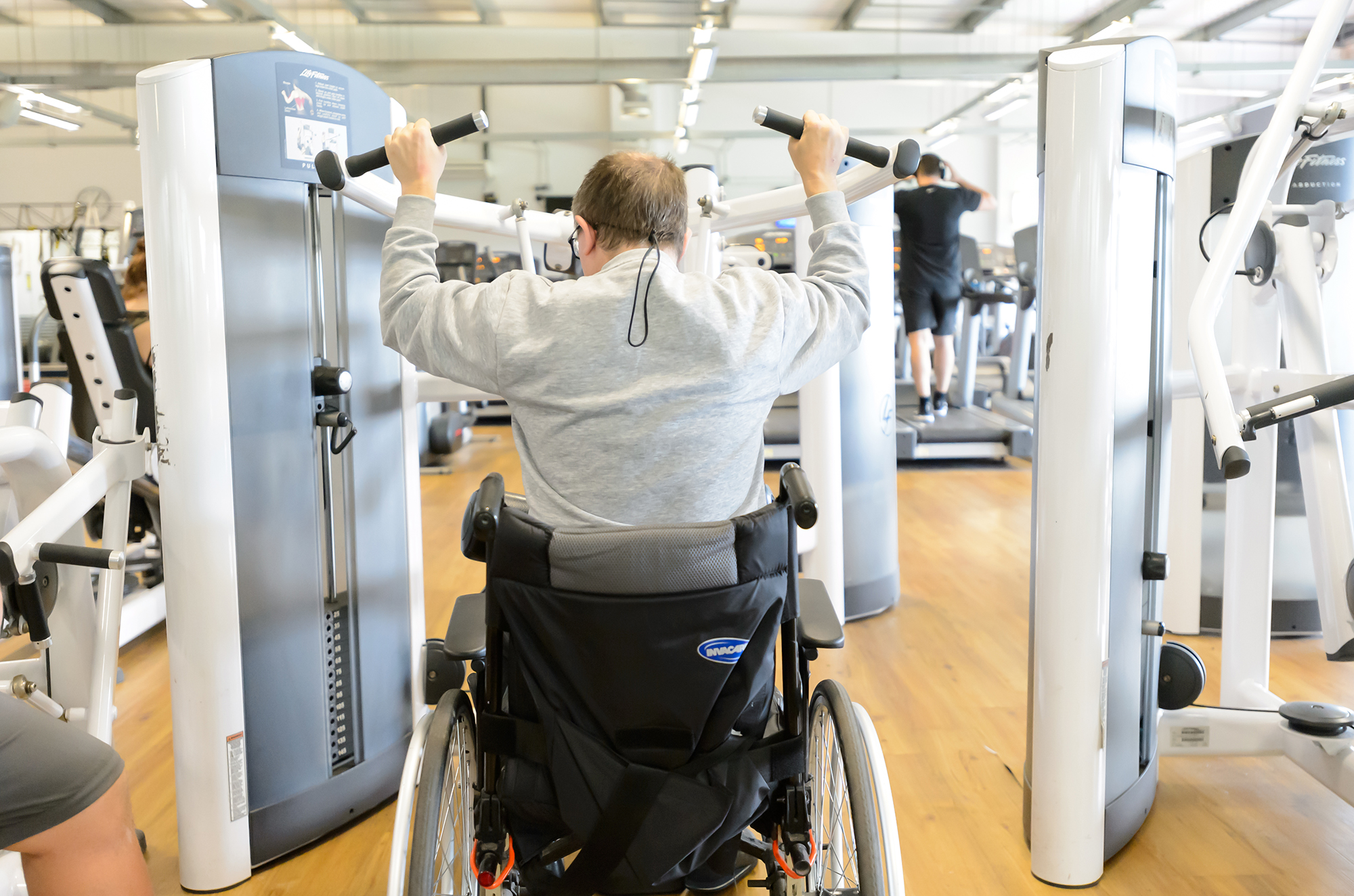 A man in a wheelchair performs a lat pulldown on a weights machine in a gym