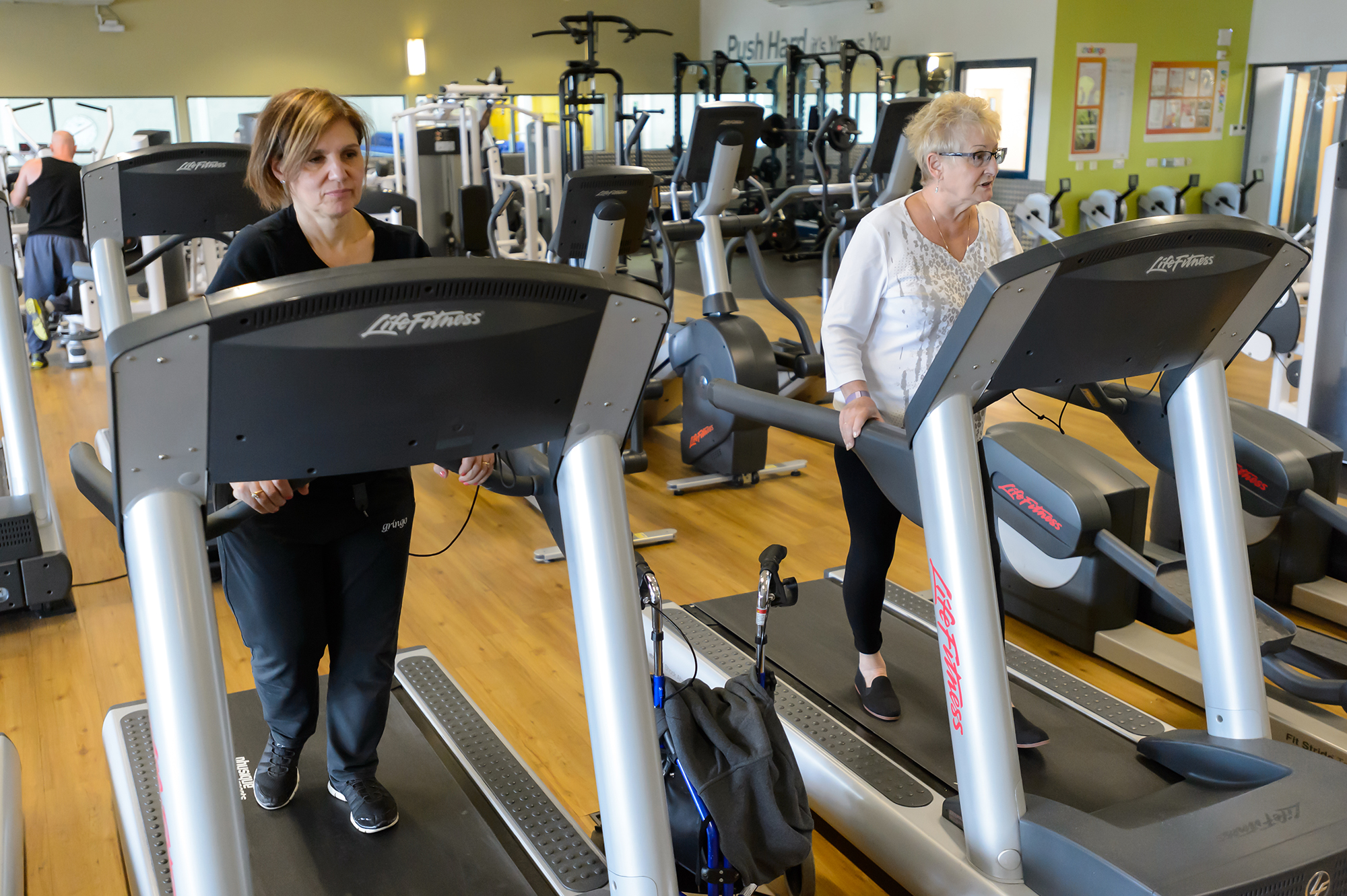 Two women exercise on treadmills in a gym
