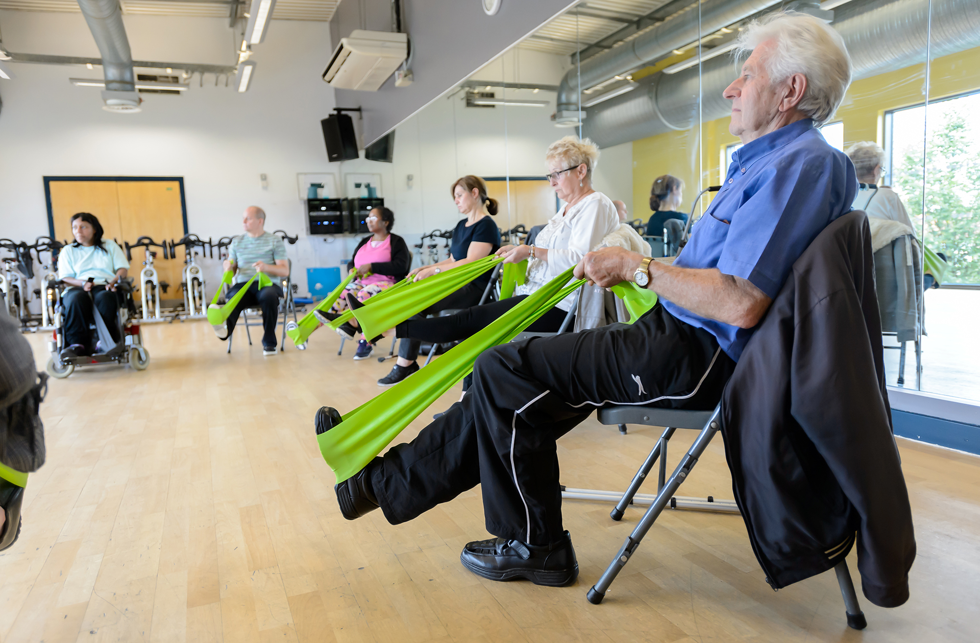 A group with MS perform seated exercise with resistance bands