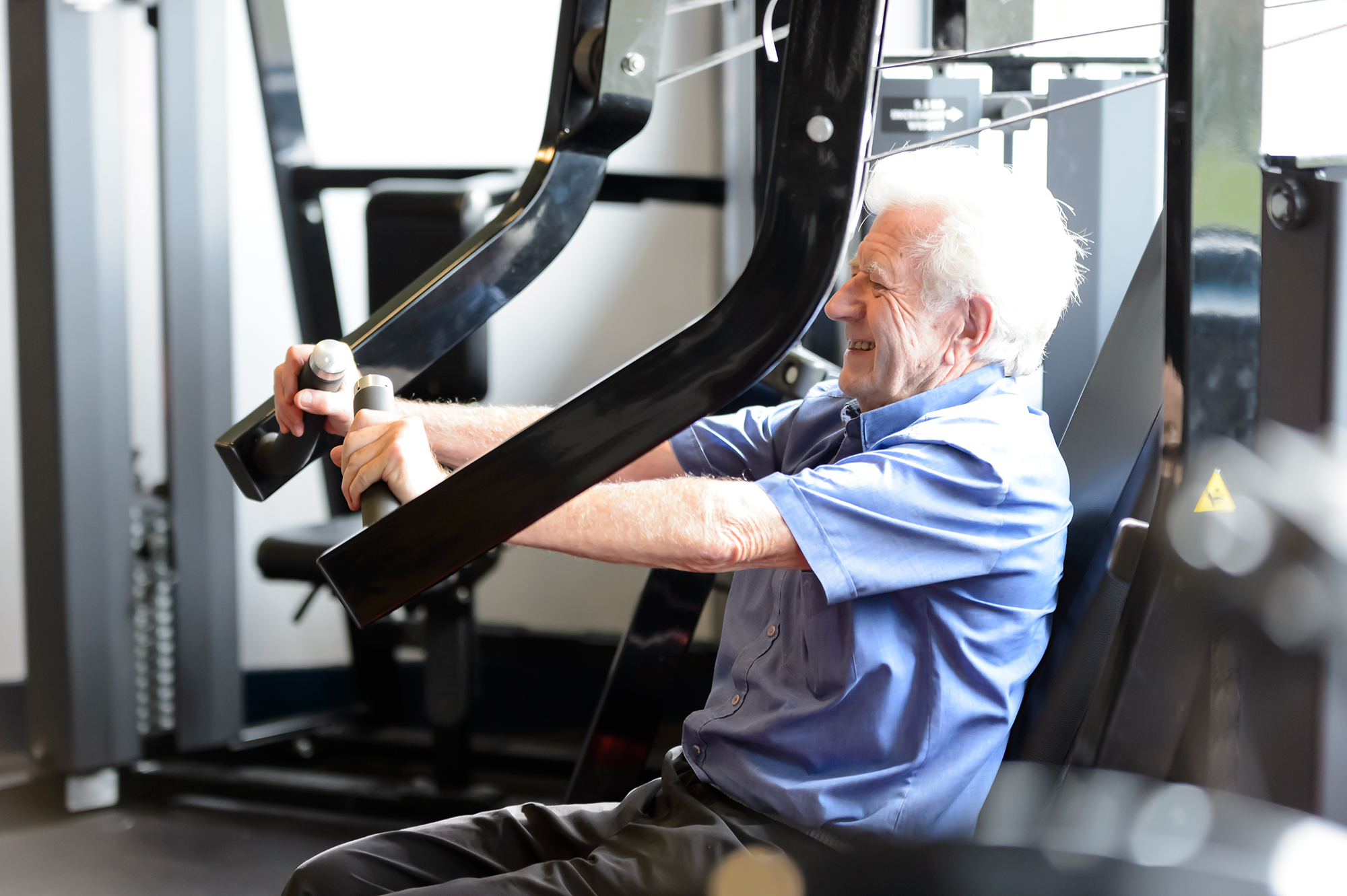 An elderly man exercises in a gym, performing a chest press