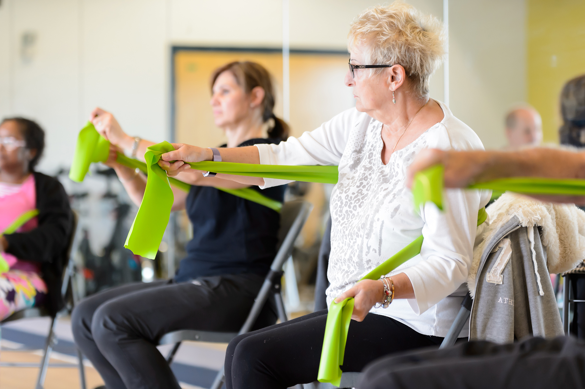 A group of adults perform seated exercise using resistance bands