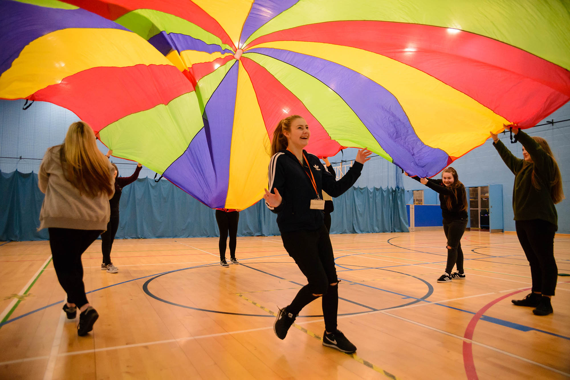 group of young women holding parachute with one person running underneath