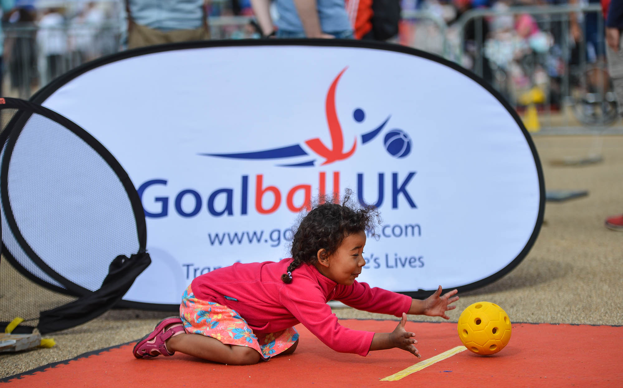 young girl playing goalball about to gather a ball